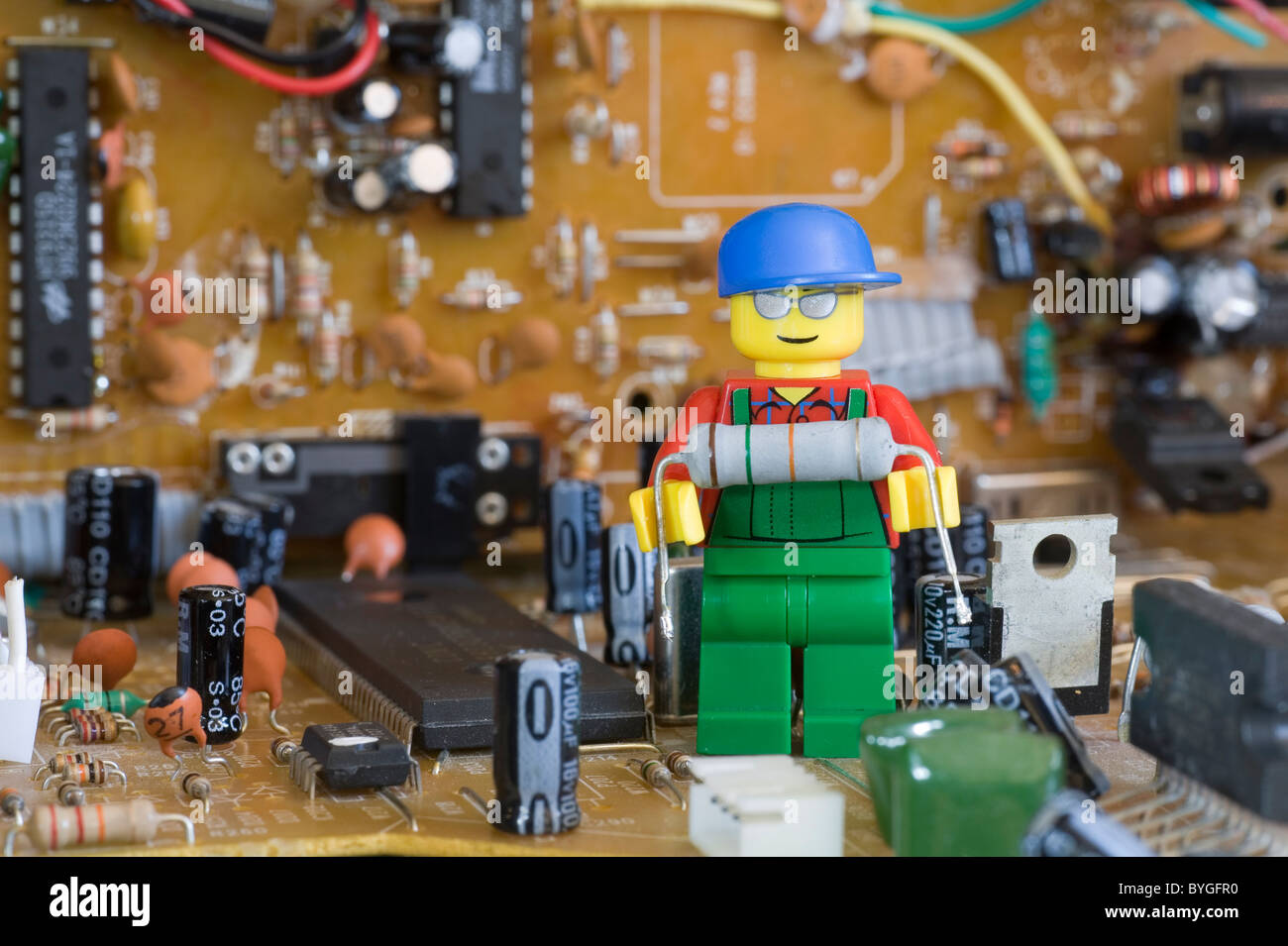 lego engineer on an electronic circuit board holding an electronic