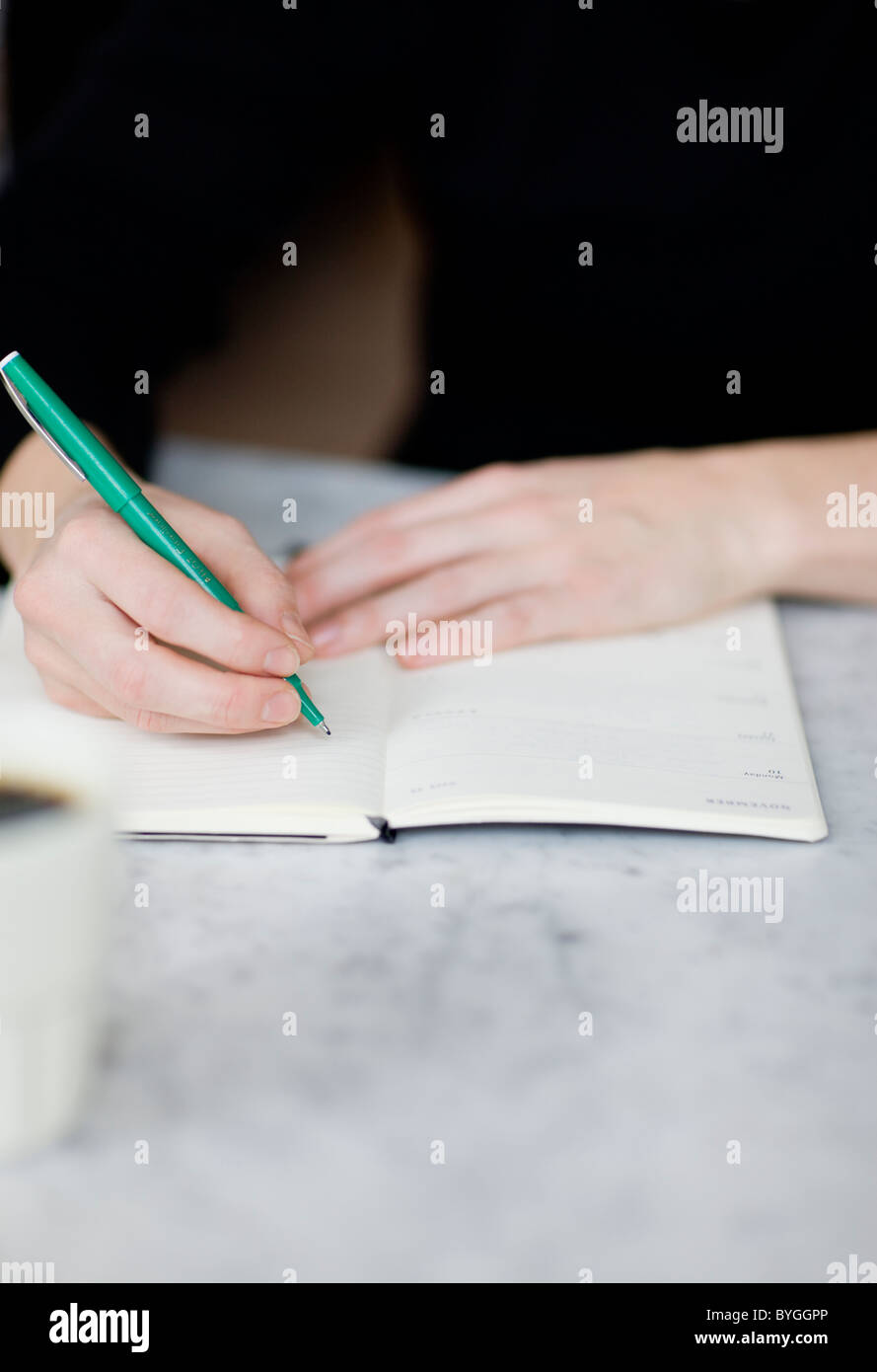 Woman writing on diary - Stock Image