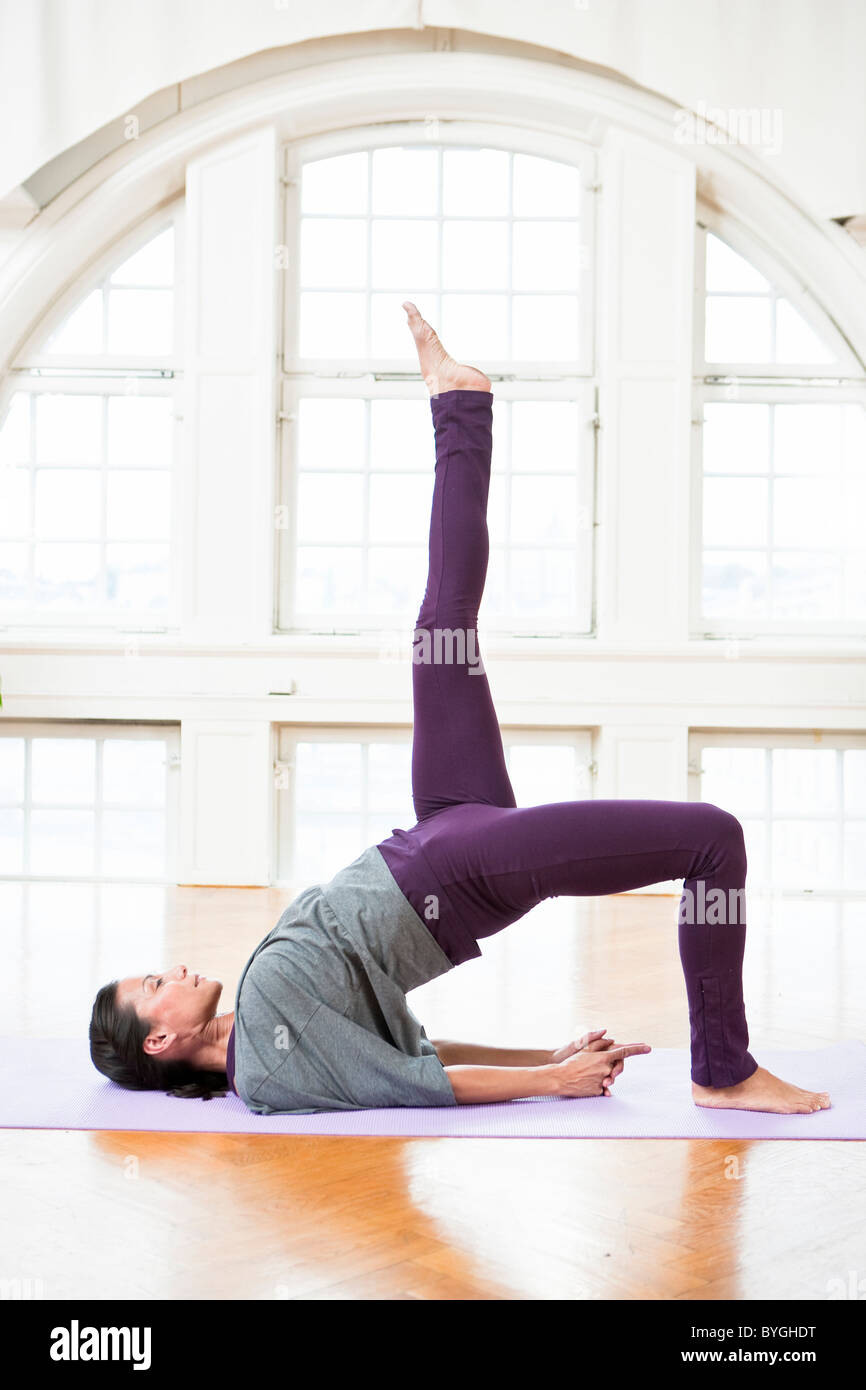 Woman exercising on mat - Stock Image