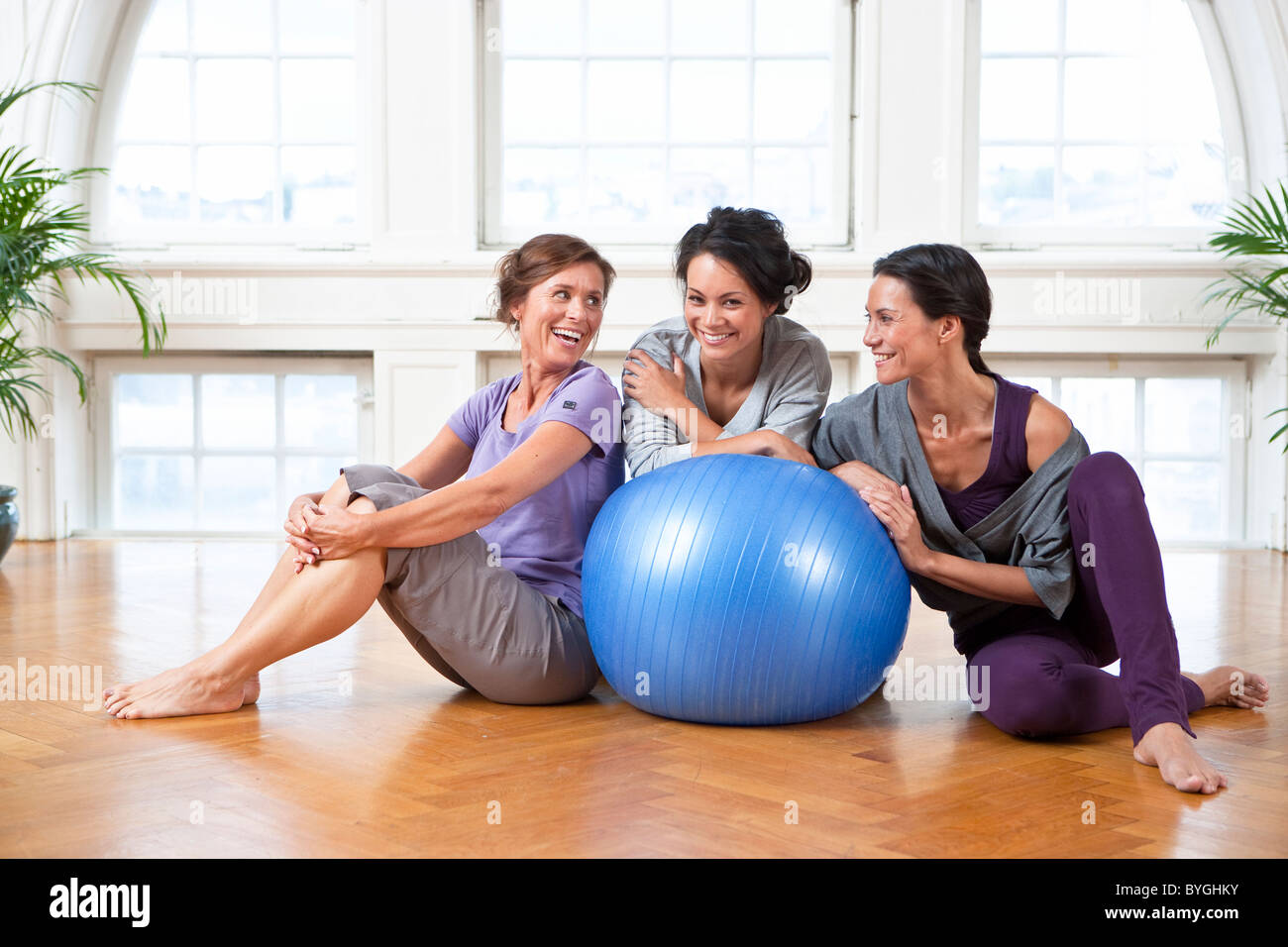 Three women with fitness ball in gym - Stock Image