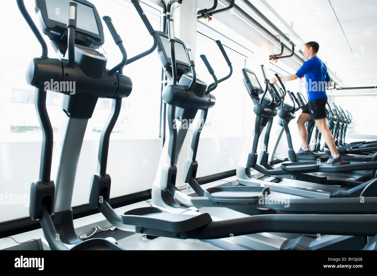 Man running on exercise machine in gym - Stock Image