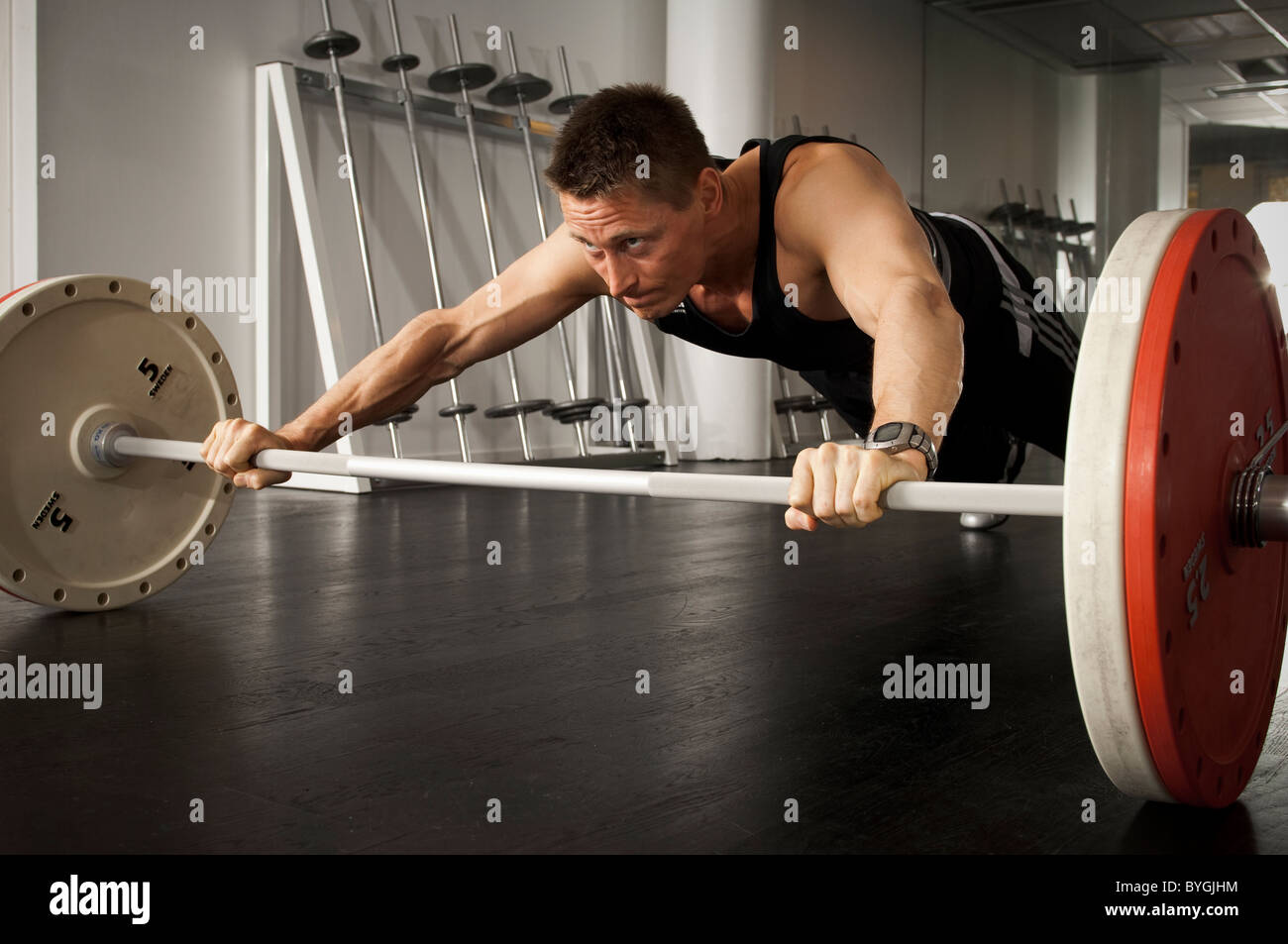 Male athlete holding barbell in gym - Stock Image