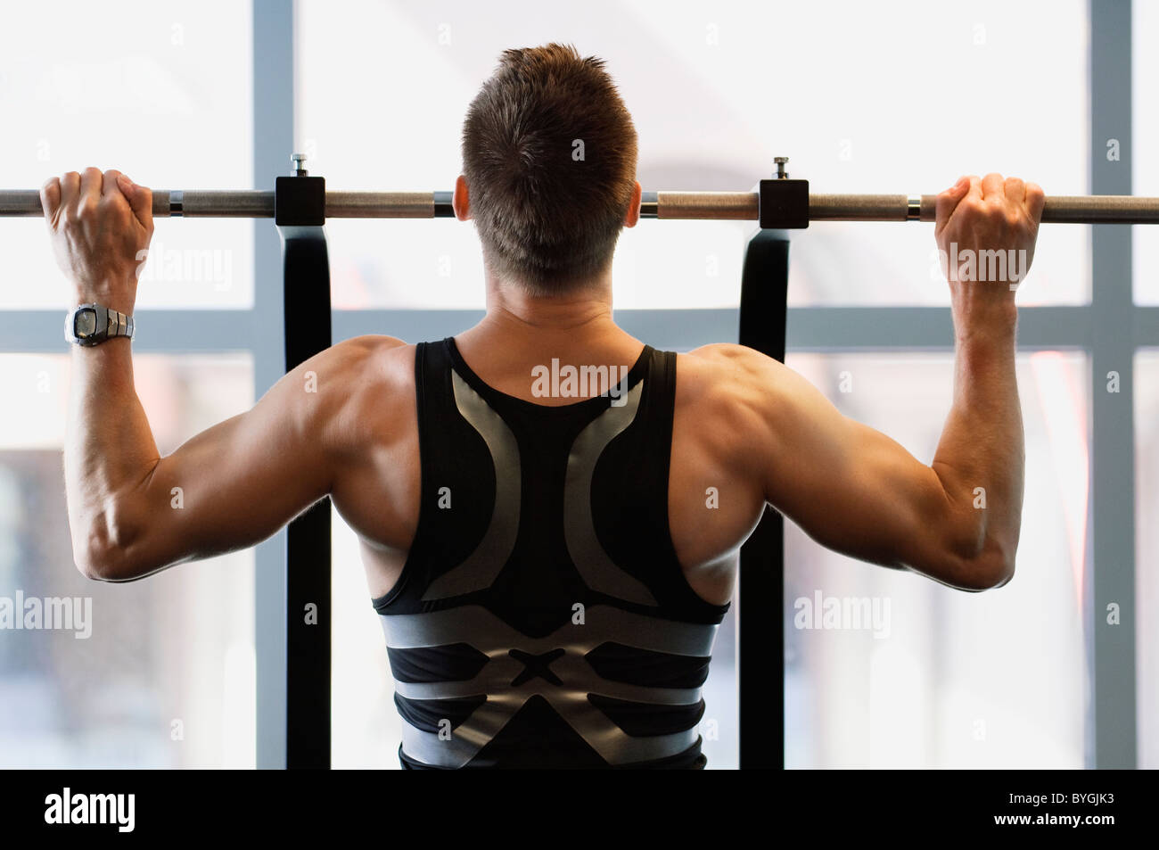 Male athlete doing pull ups in gym - Stock Image