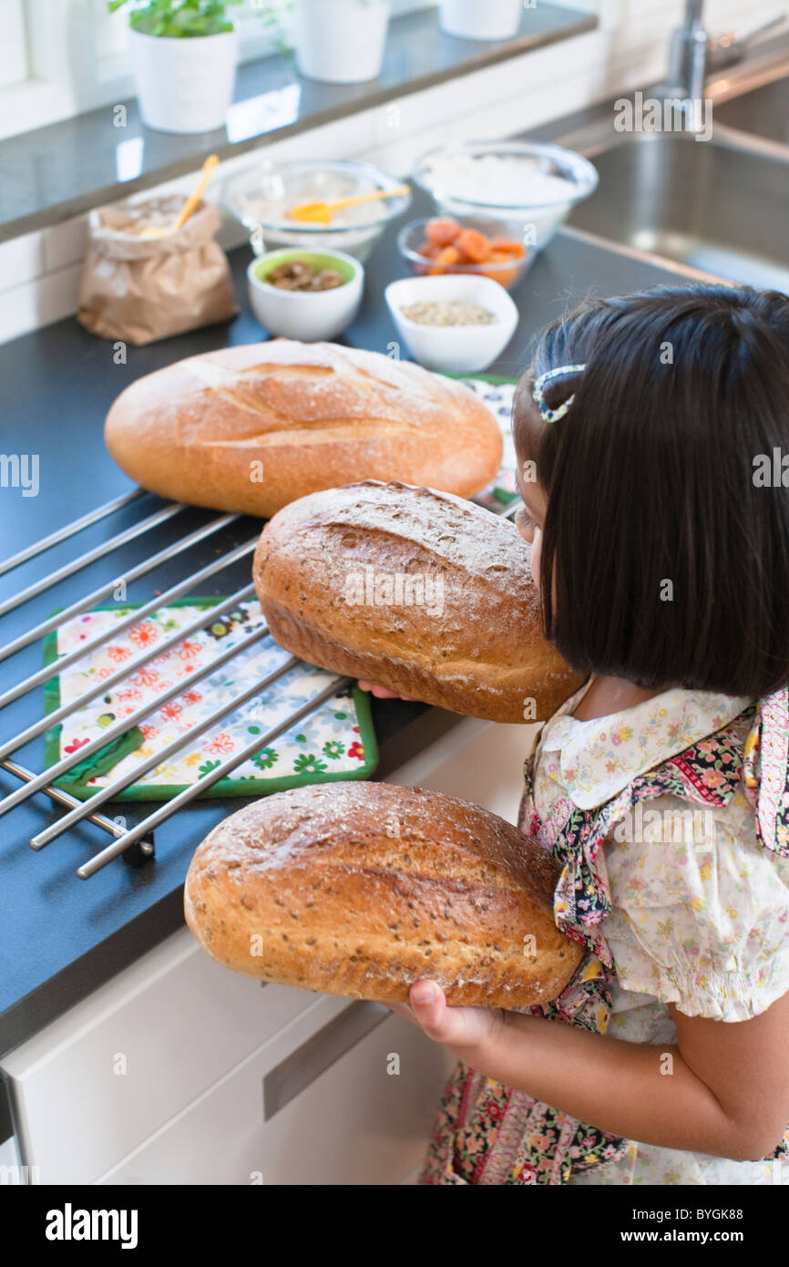 Girl holding freshly made bread, high angle view - Stock Image
