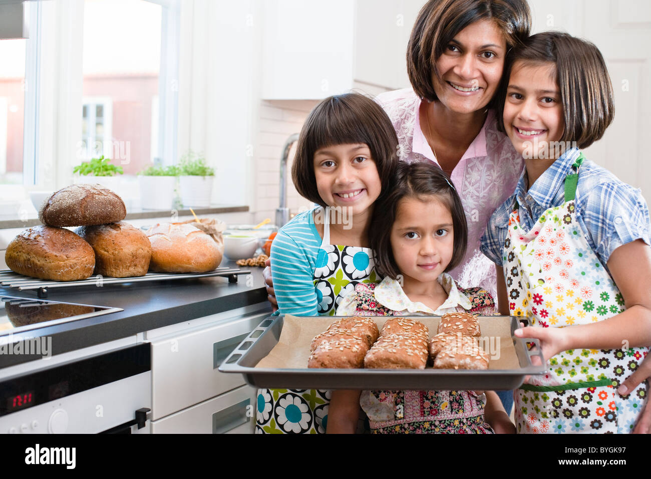 Portrait of mother with three daughters with freshly made rolls - Stock Image