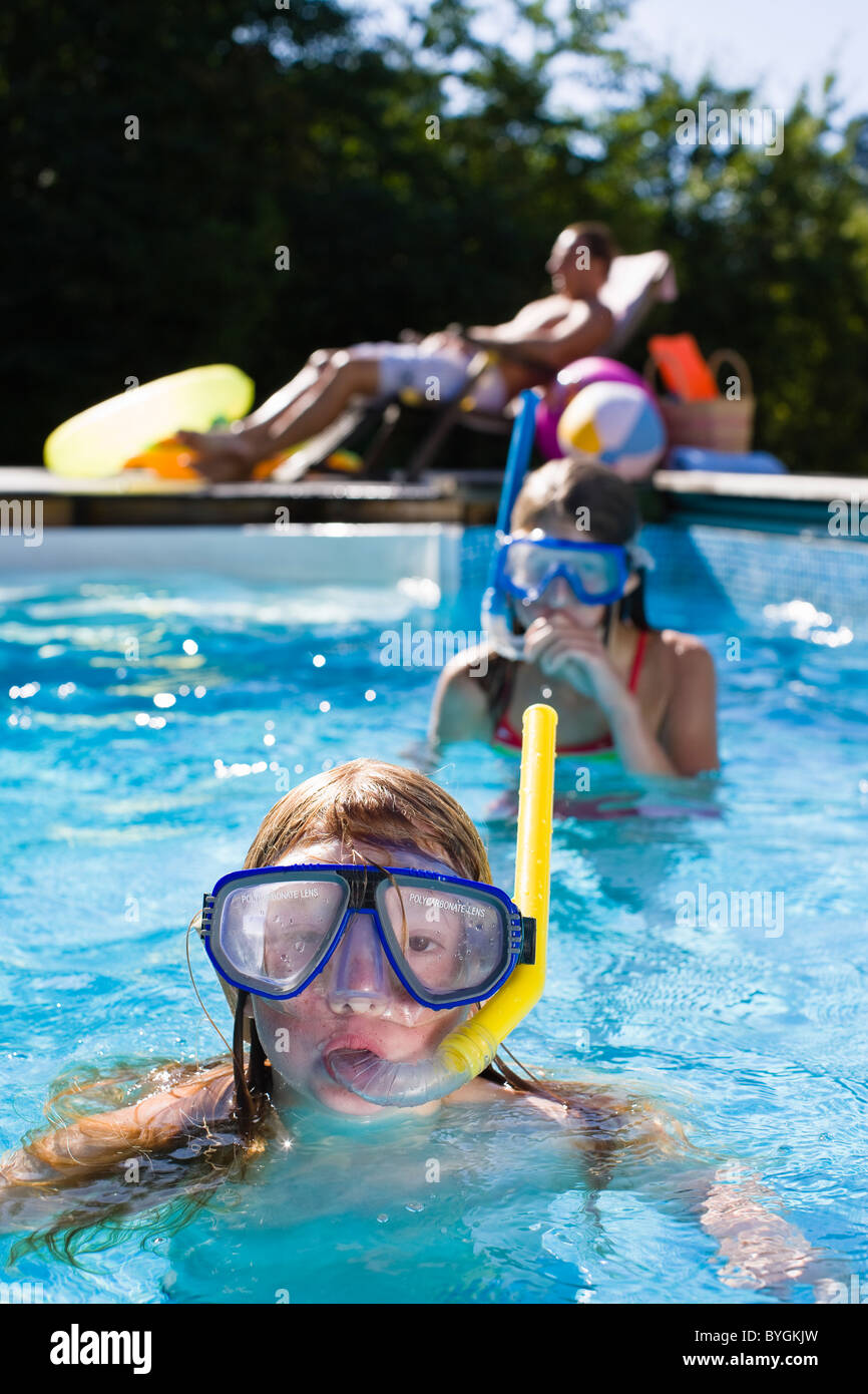 Children in scuba masks swimming in swimming pool - Stock Image