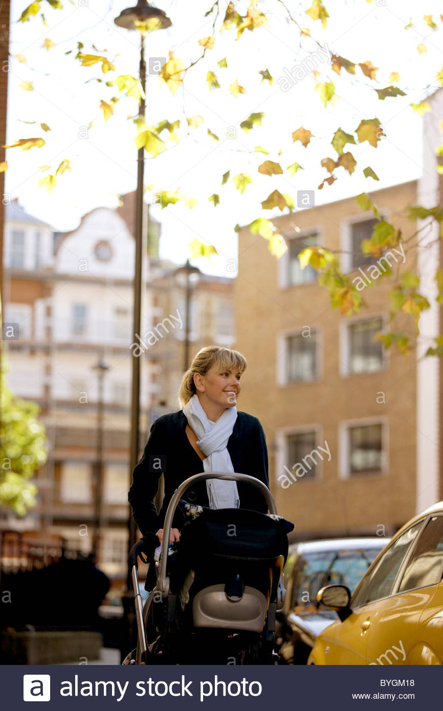A mother pushing a stroller in the street - Stock Image