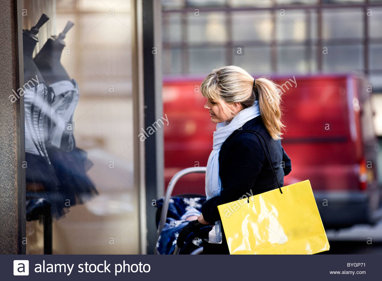 A mother pushing a stroller, looking in a shop window - Stock Image