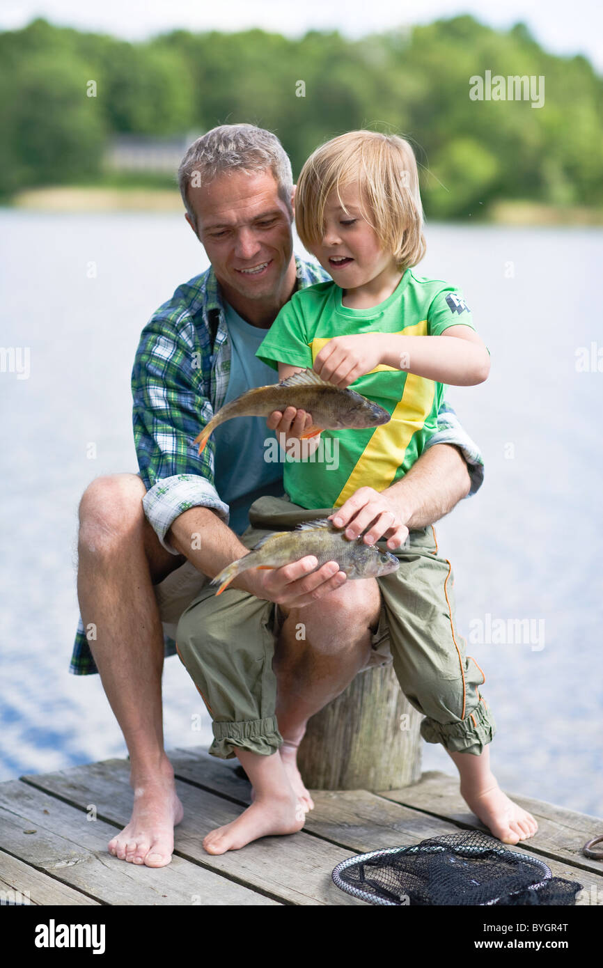 Father and son sitting  on jetty, boy holding fish - Stock Image