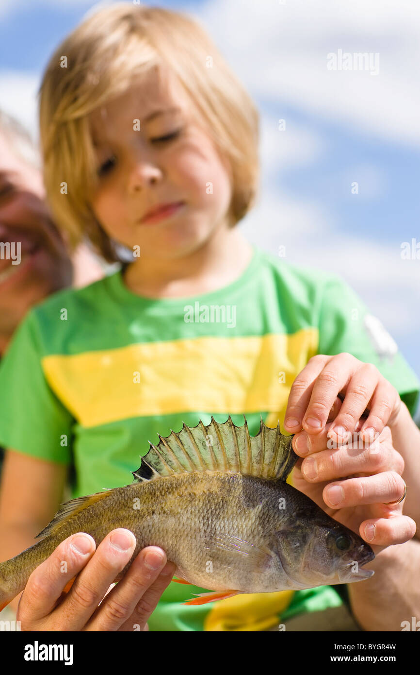 Father and son holding fish, focus on foreground - Stock Image