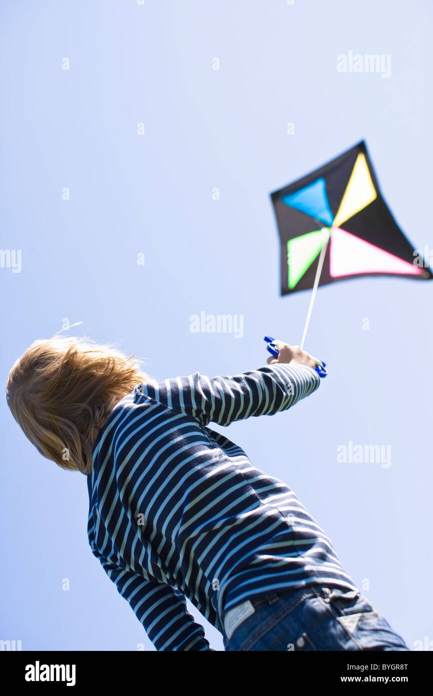 Boy flying kite in bright sunlight, against clear sky Stock Photo