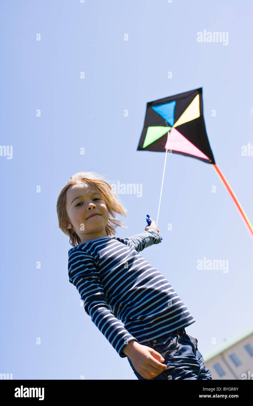 Portrait of boy  flying kite in bright sunlight, against clear sky Stock Photo
