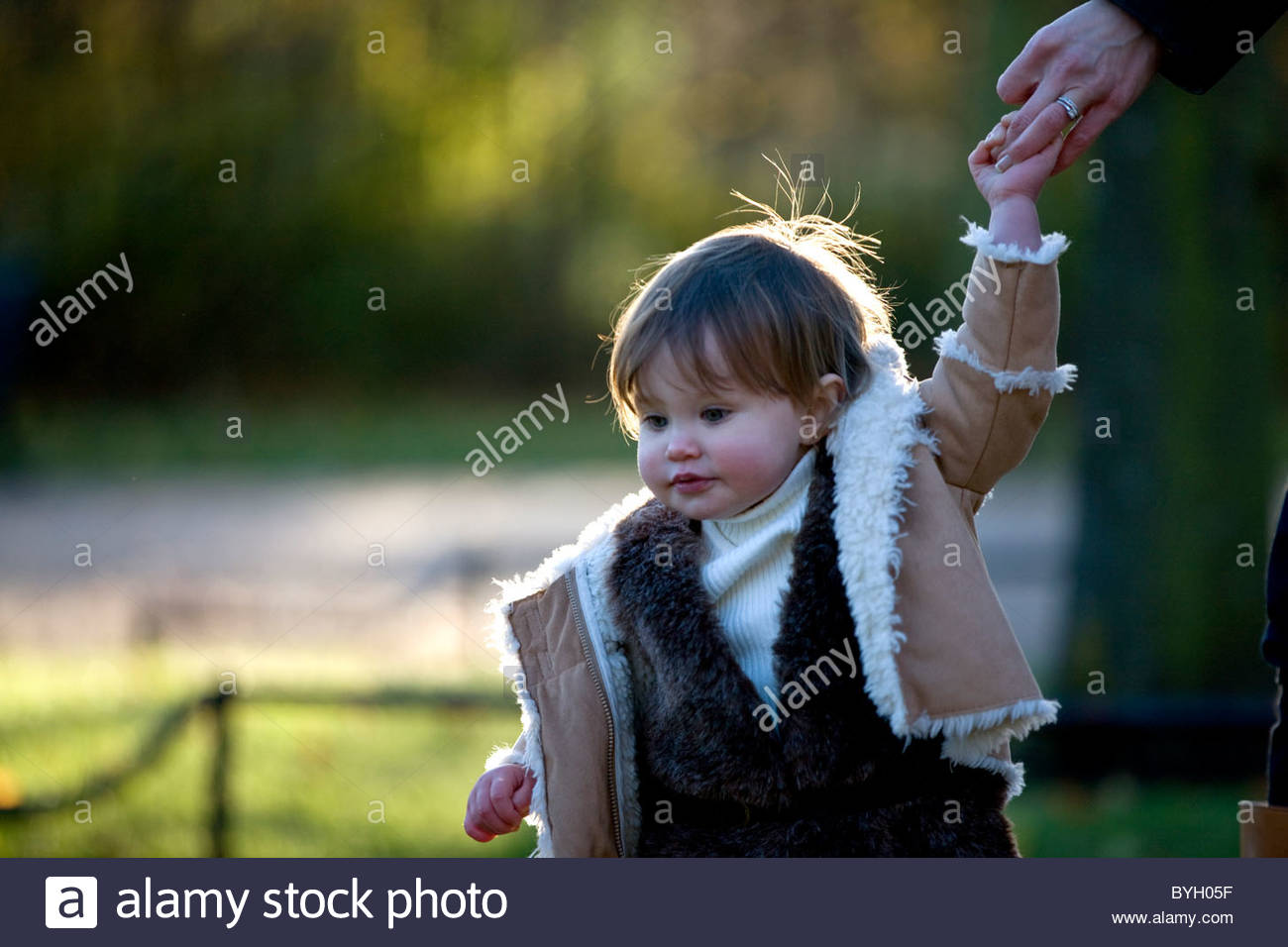 A baby girl holding her mother's hand in the park - Stock Image