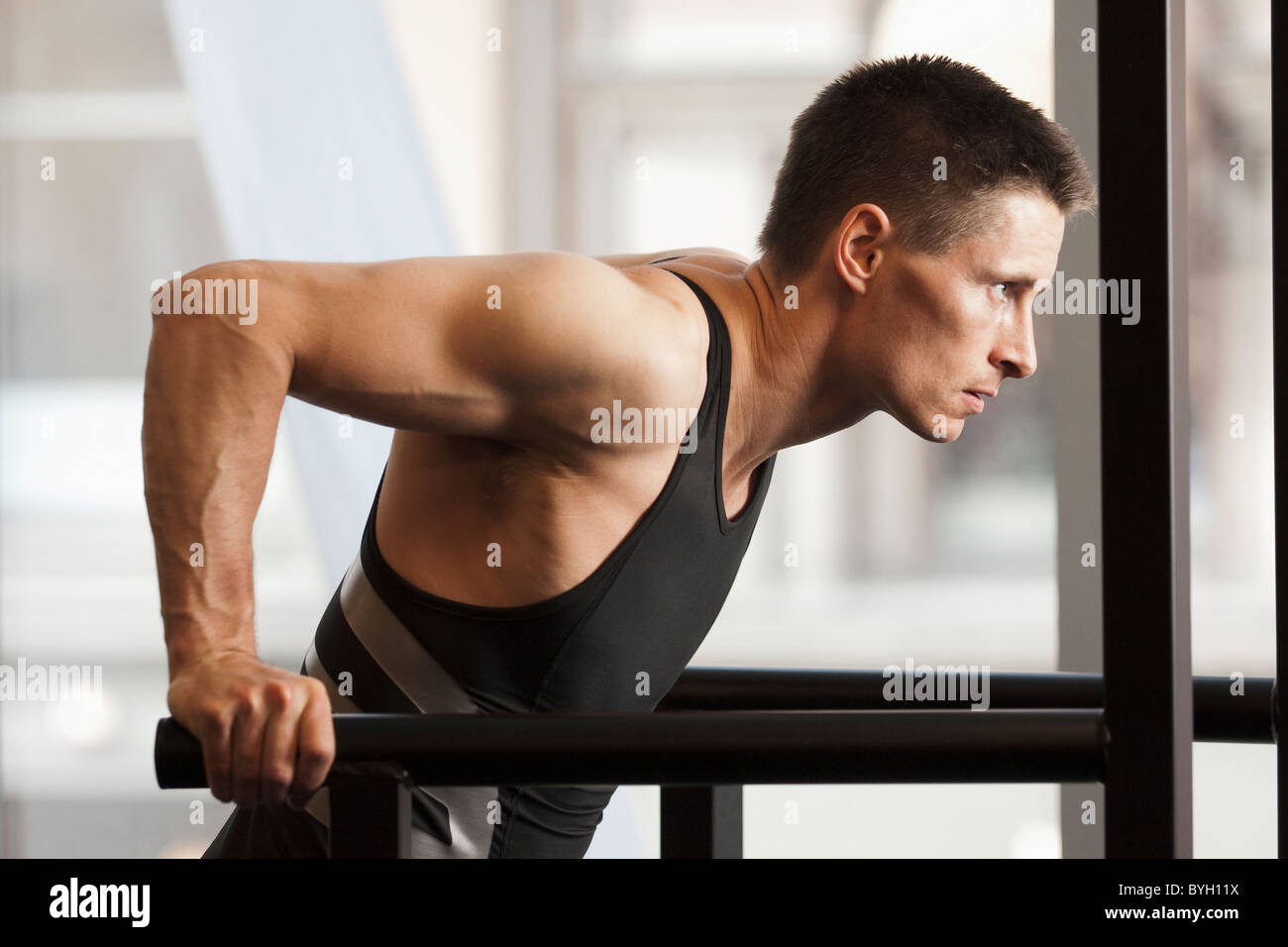 Male athlete using gymnastics equipment in gym - Stock Image