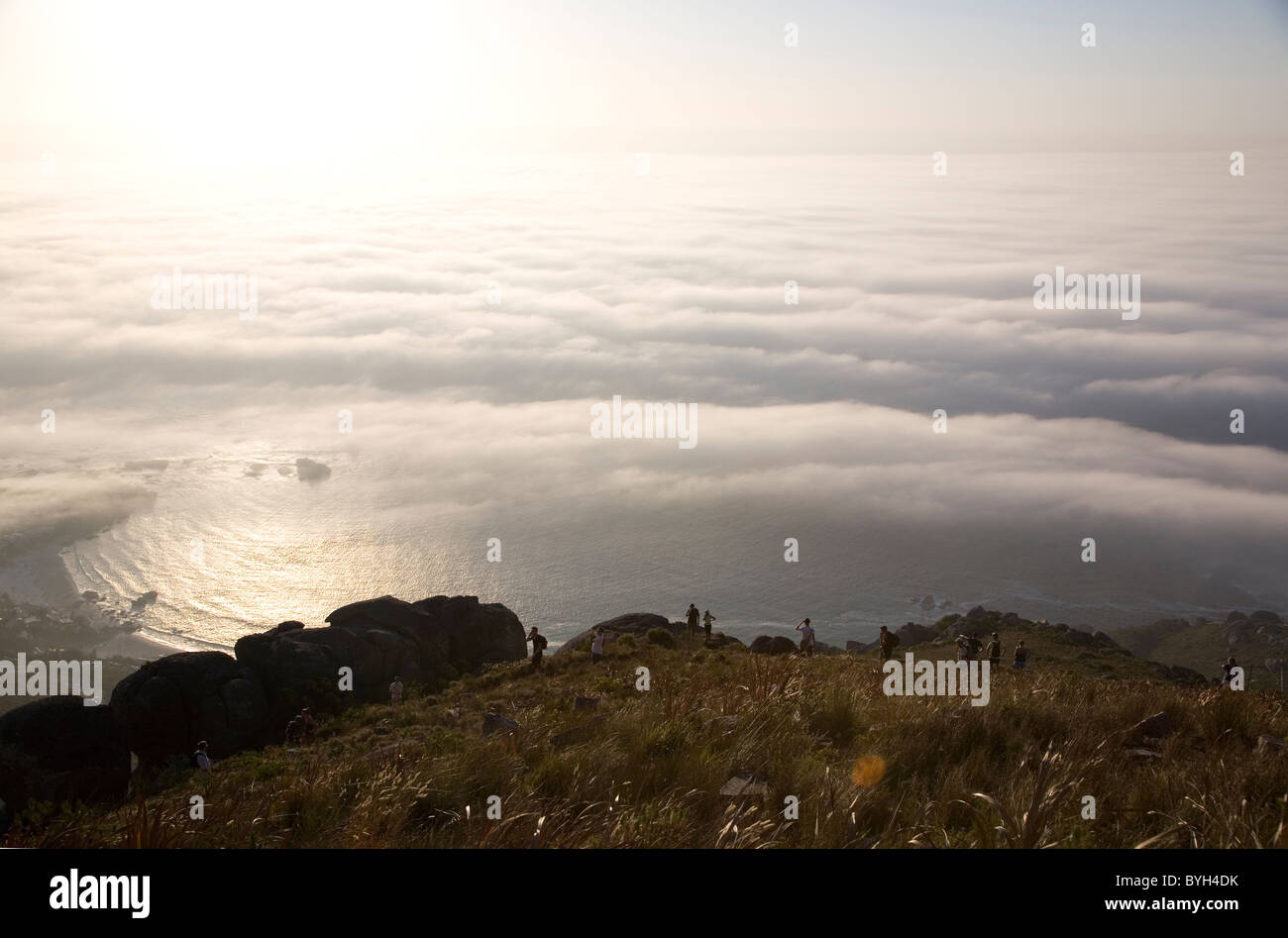 Hikers on Lions Head watching approaching fog onto Cape Peninsula - Stock Image