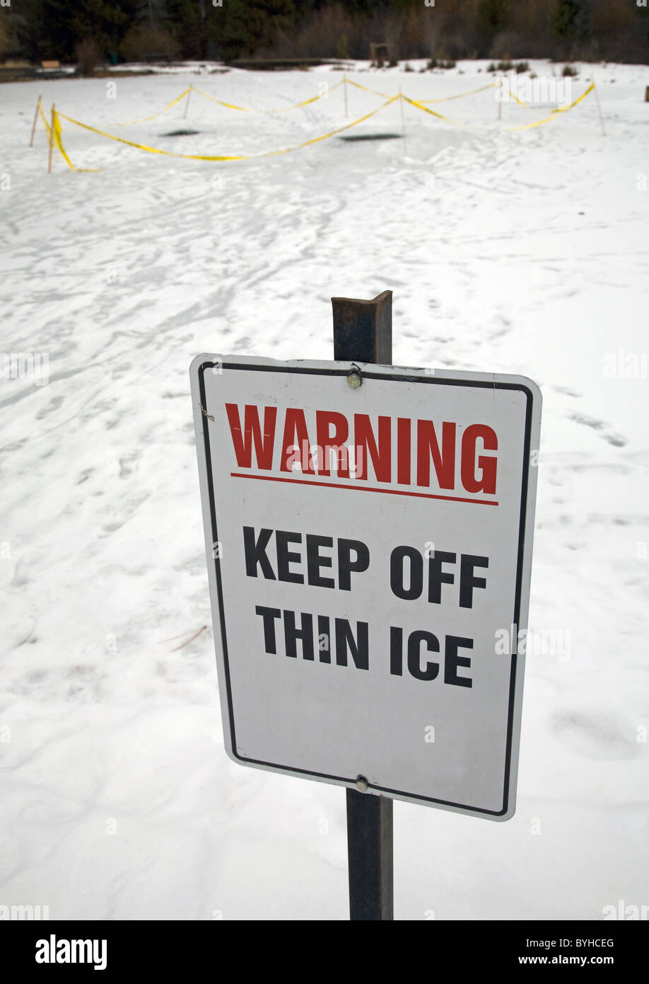A thin ice sign warns skaters away from a pond - Stock Image