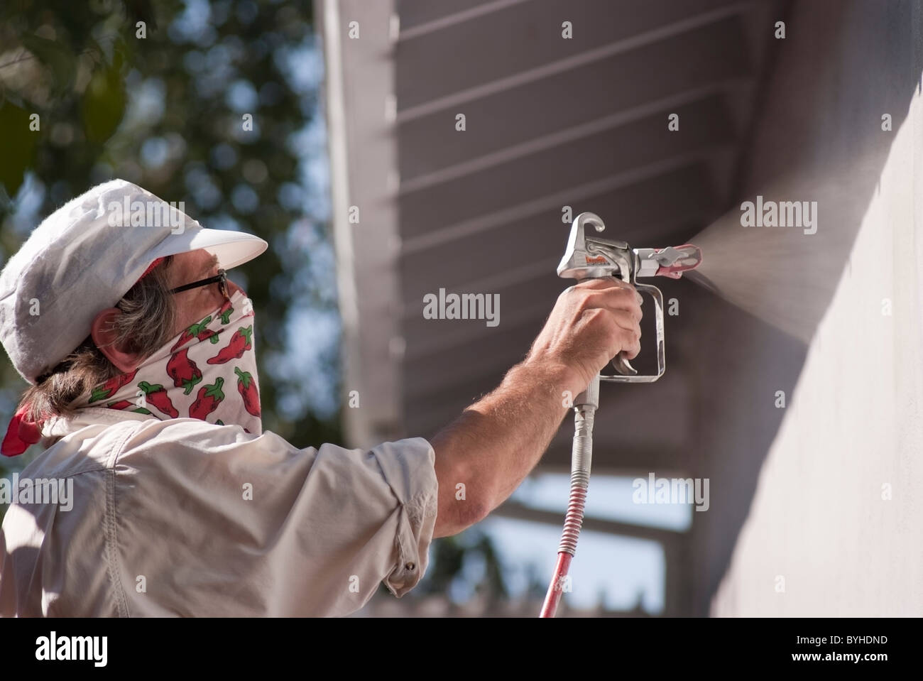 Homeowner painting the exterior of a single family, ranch style home in San Jose, CA before putting the home up - Stock Image