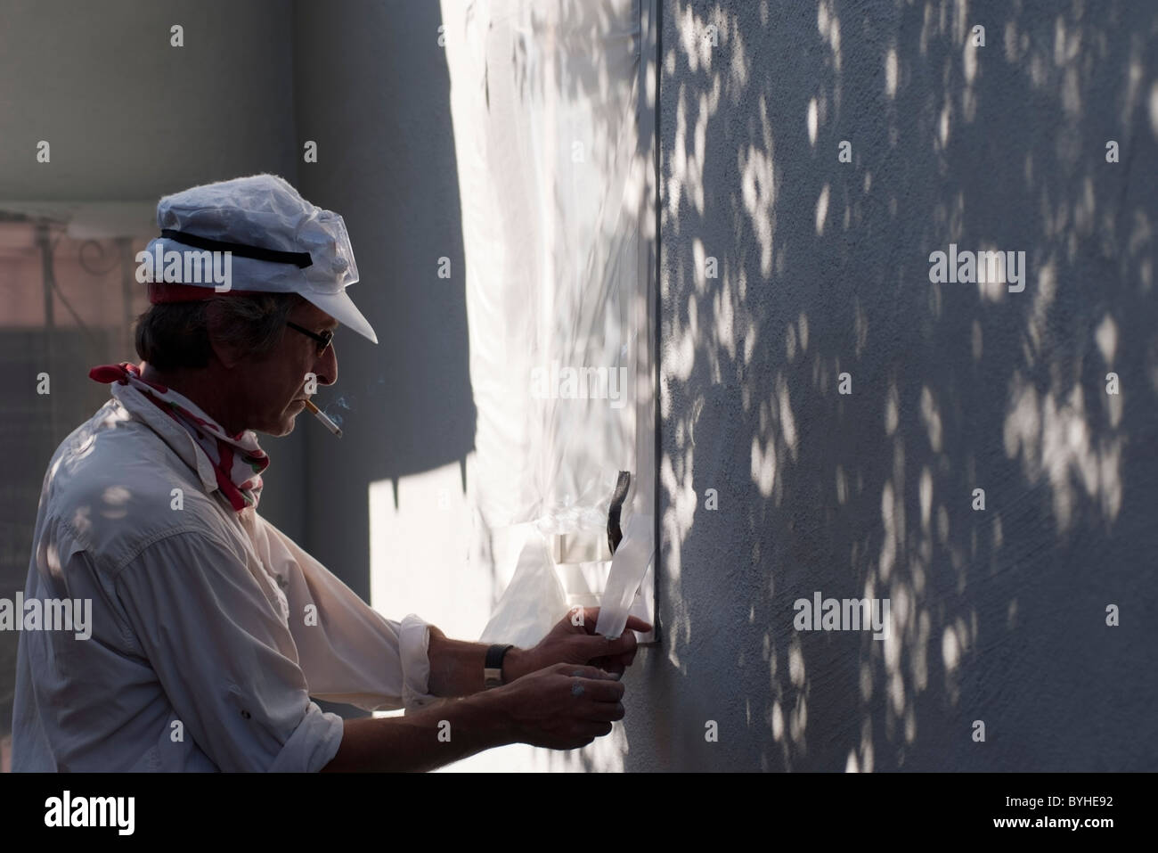 Homeowner strips masking tape from a window after painting his single family ranch style home in San Jose, CA. - Stock Image