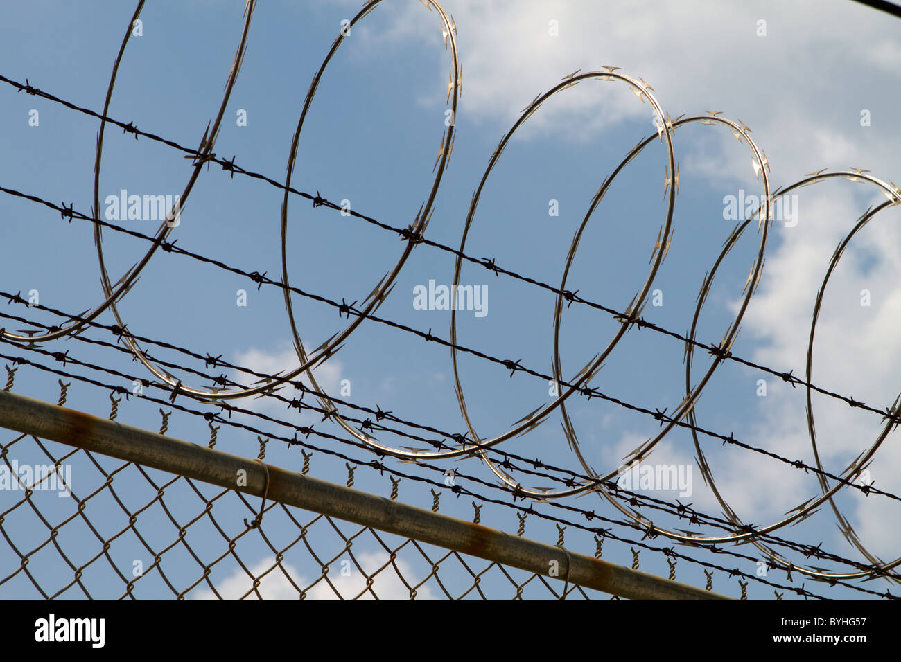 Razor wire and barbed wire top a fence to prevent people from Stock ...