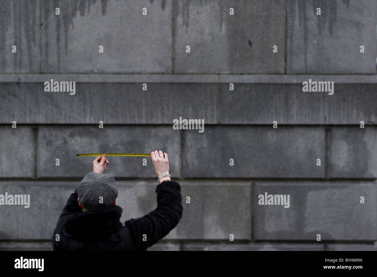 A woman measures a section of wall with a tape measure. - Stock Image