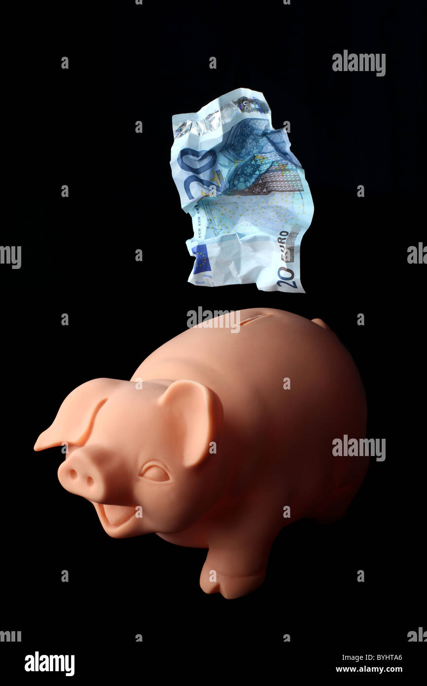 Piggybank with a crumpled twenty euro note above it. - Stock Image