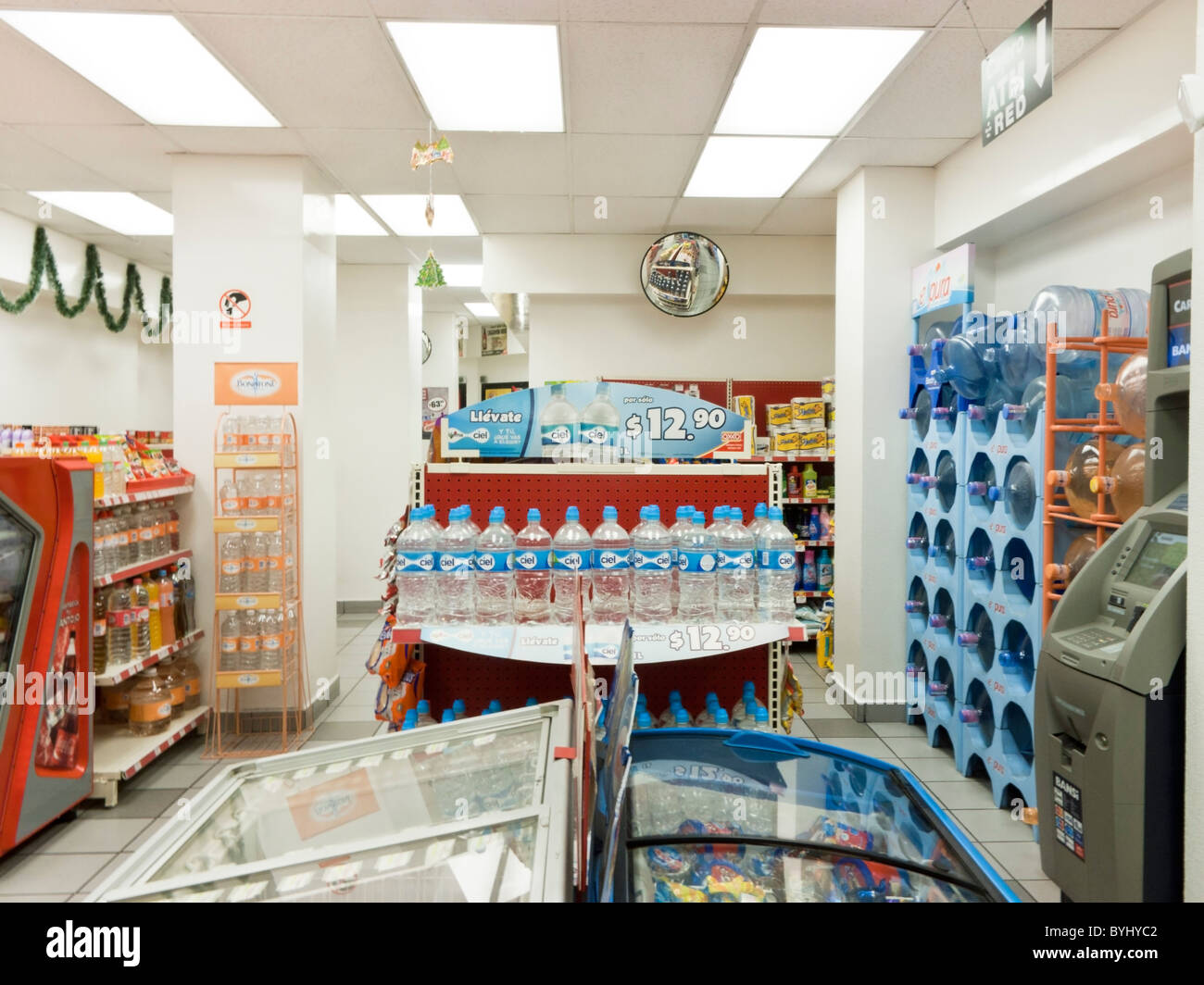 area of small brightly lit Mexican convenience chain store featuring bottled water Avenida Alvaro Obregon Mexico - Stock Image