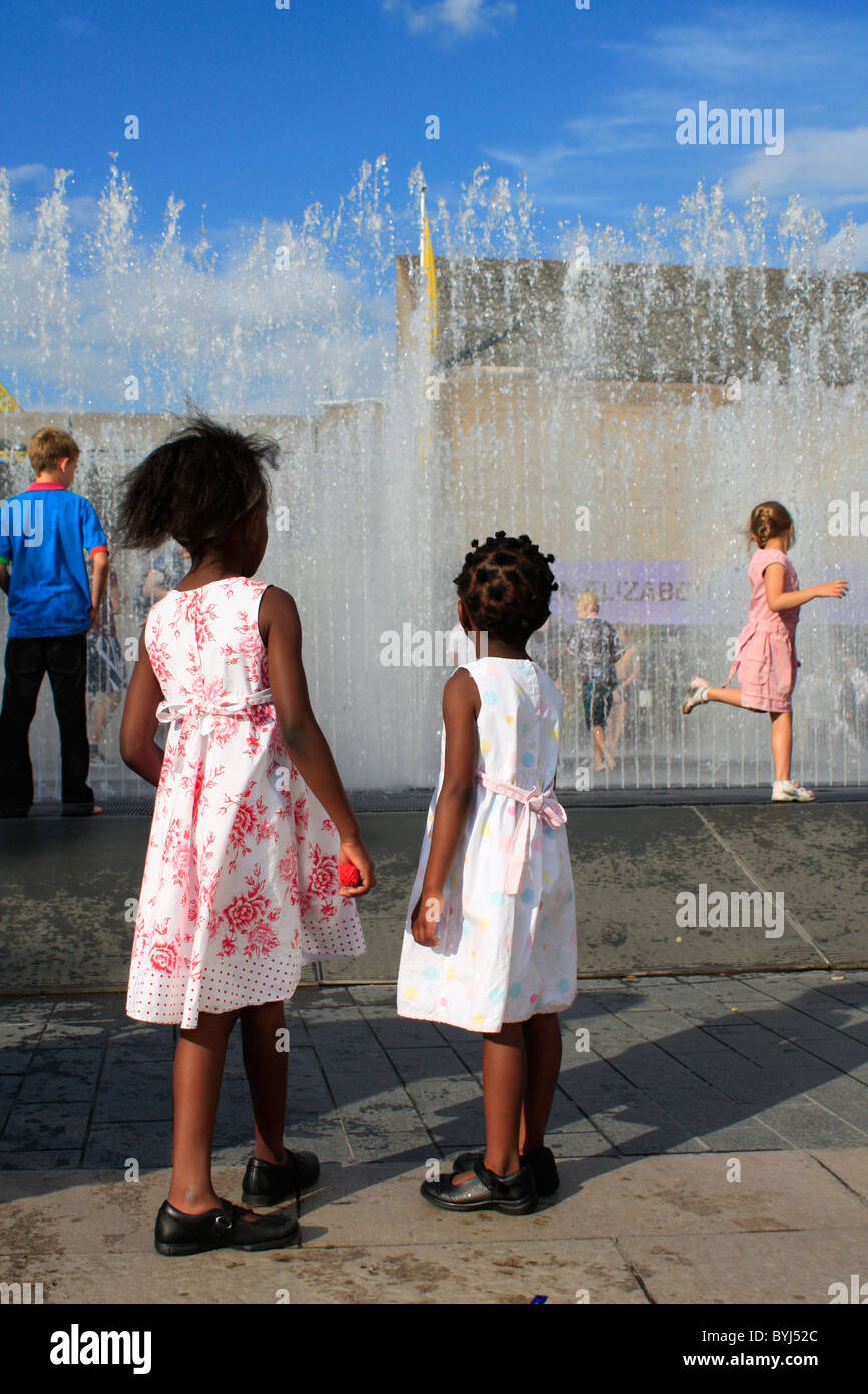 sisters watching the fountain at London's Southbank - Stock Image