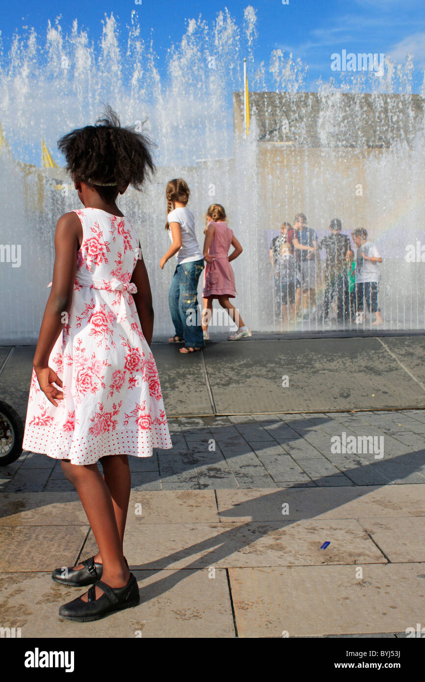 Girl standing in front of fountain at London's Southbank - Stock Image