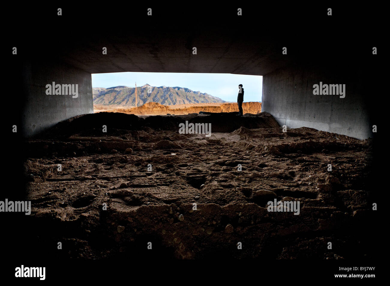 Man standing at entrance to dark tunnel - Stock Image