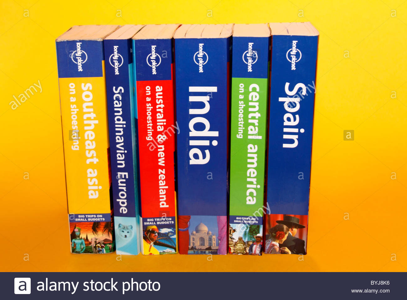 Studio shot of row of Lonely Planet guide books on a yellow background Stock Photo