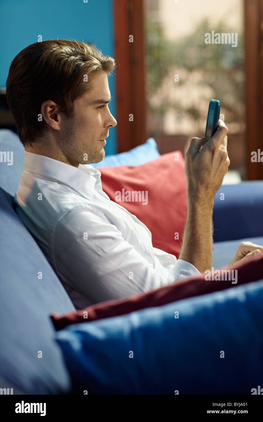man sitting on sofa at home and writing text message on mobile phone. Vertical shape, side view, waist up - Stock Image