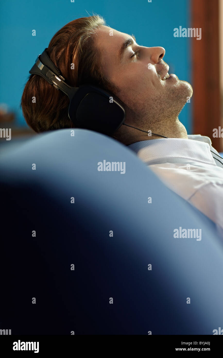 caucasian adult man relaxing on sofa with headphones. Vertical shape, side view, copy space - Stock Image