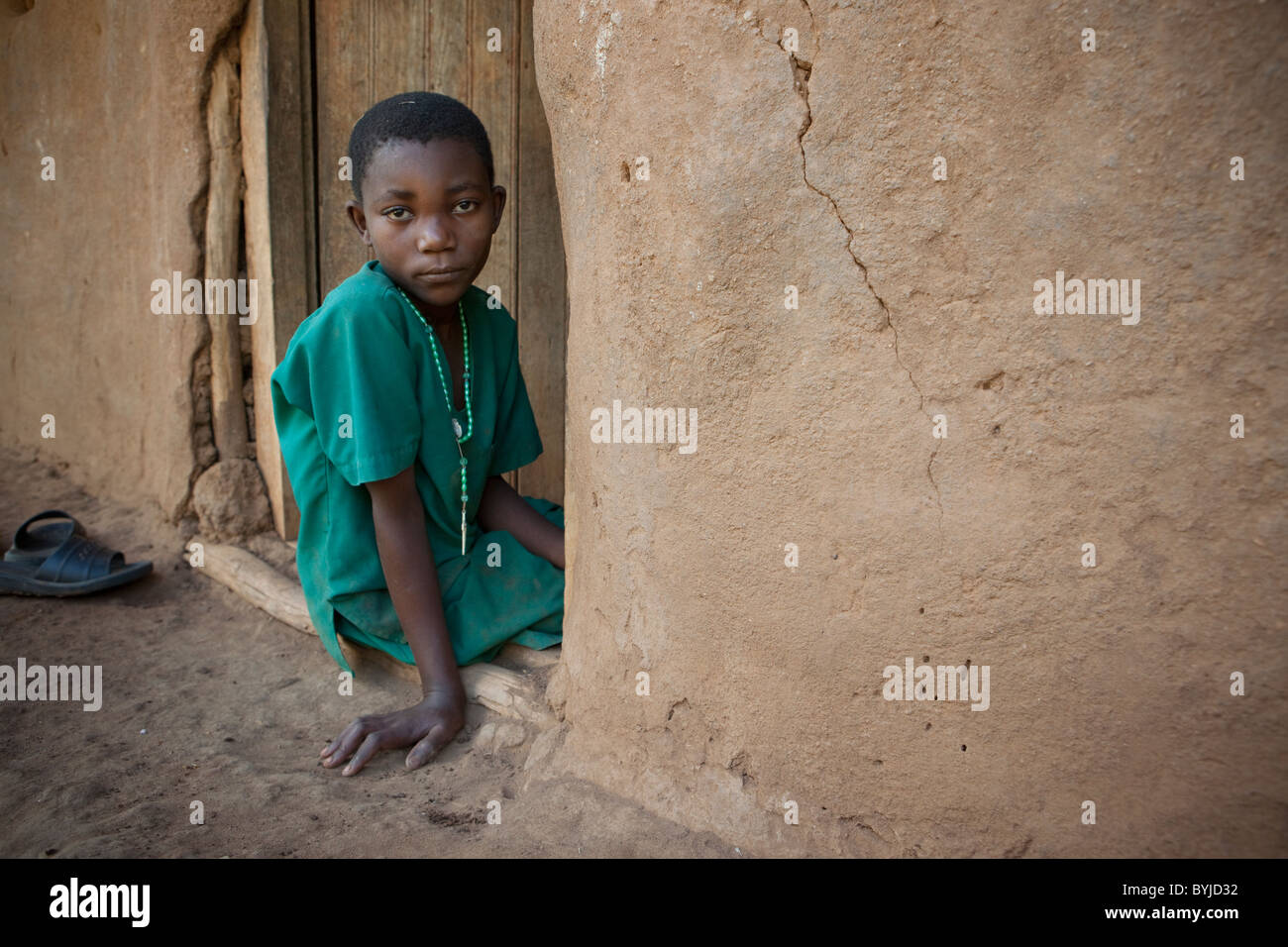 A child sits in the doorway of her home in Masaka Uganda - Stock Image