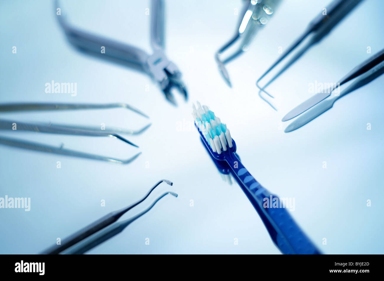 Toothbrush surrounded by dental instruments with very shallow depth of field - Stock Image