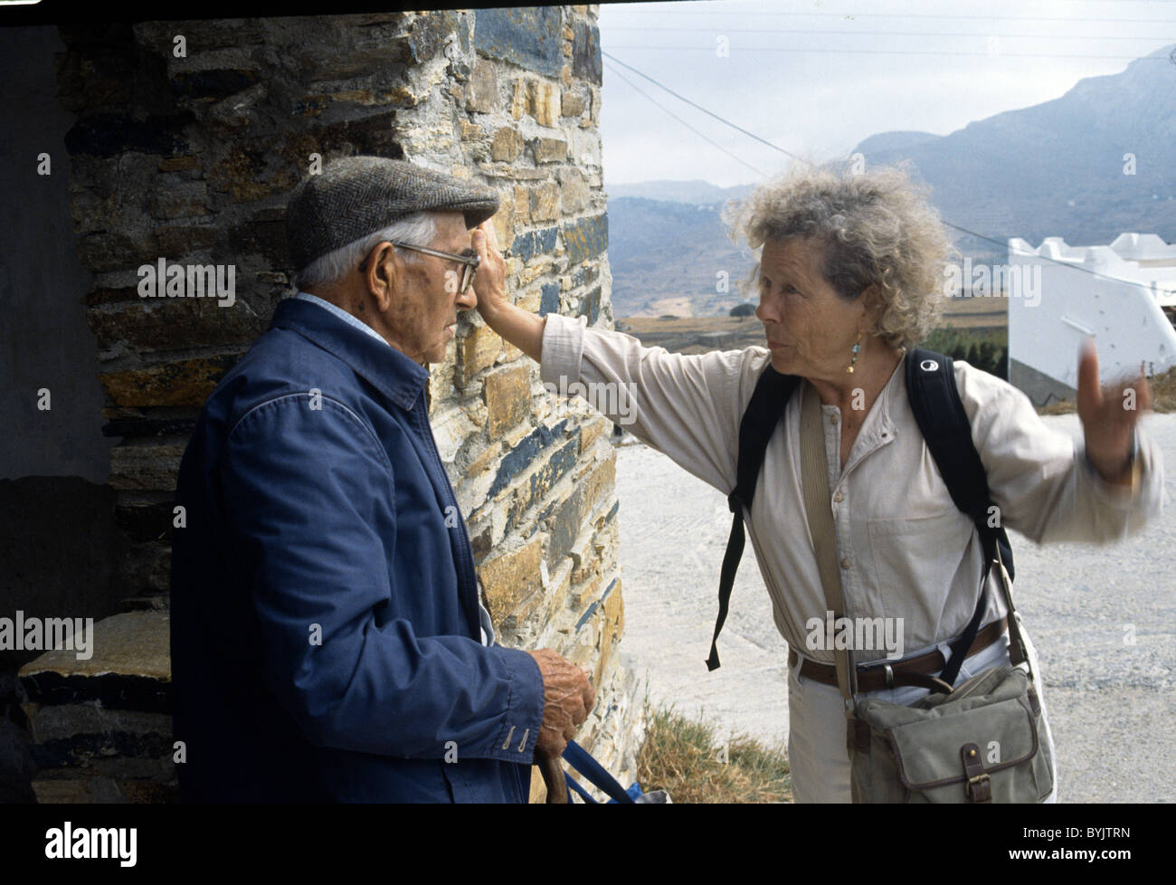elderly English woman talking with a old Greek local man in Greece - Stock Image