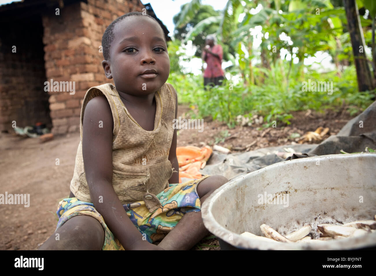 A young boy sits by a cooking pot full of bananas in rural Masaka, Uganda, East Africa. Stock Photo