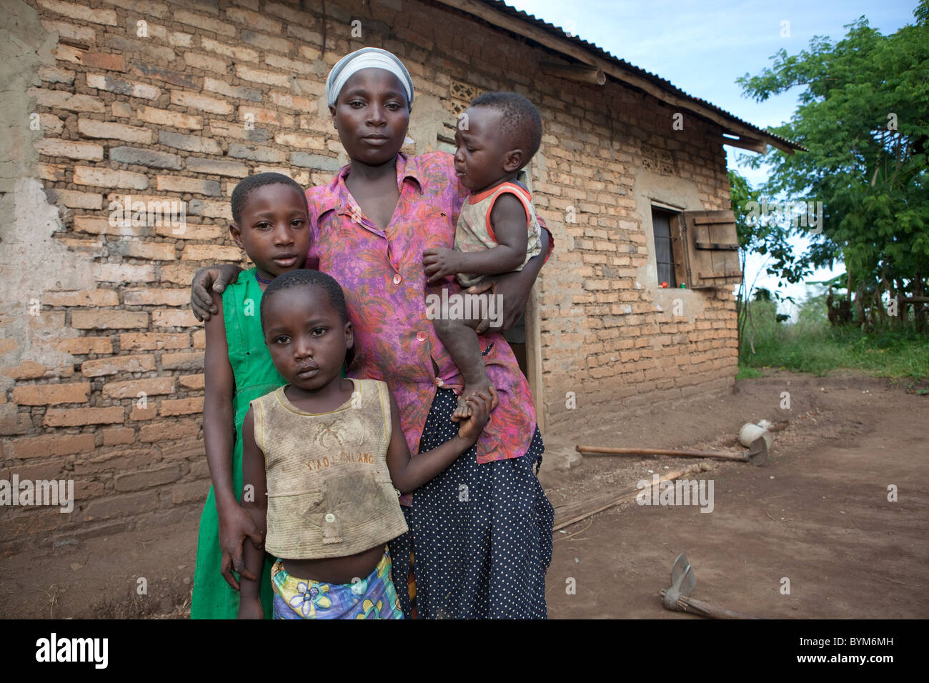 A young single mother and her children stand in front of their brick house in rural Masaka, Uganda, East Africa. - Stock Image