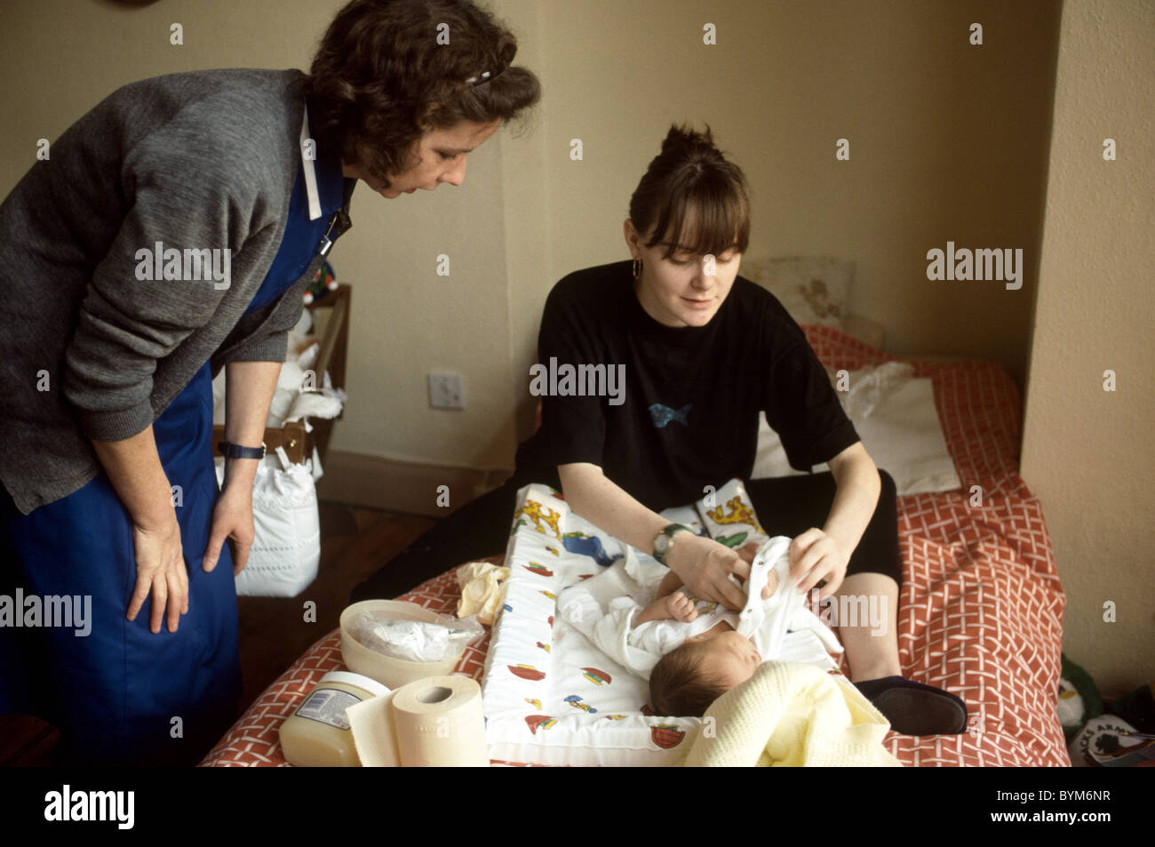 Midwife at a home visit with mother and newborn - Stock Image