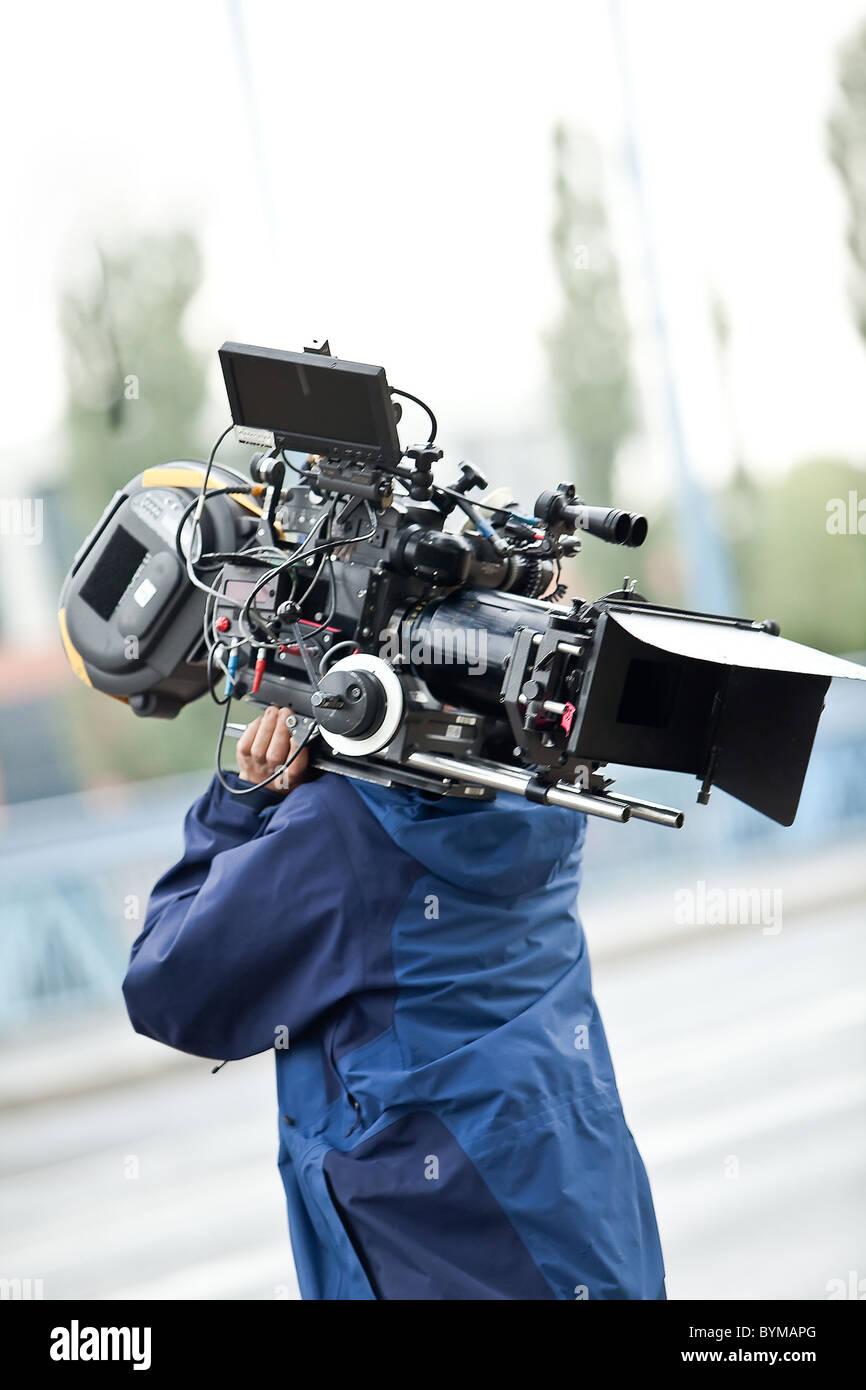 Camera operator carrying equipment - Stock Image