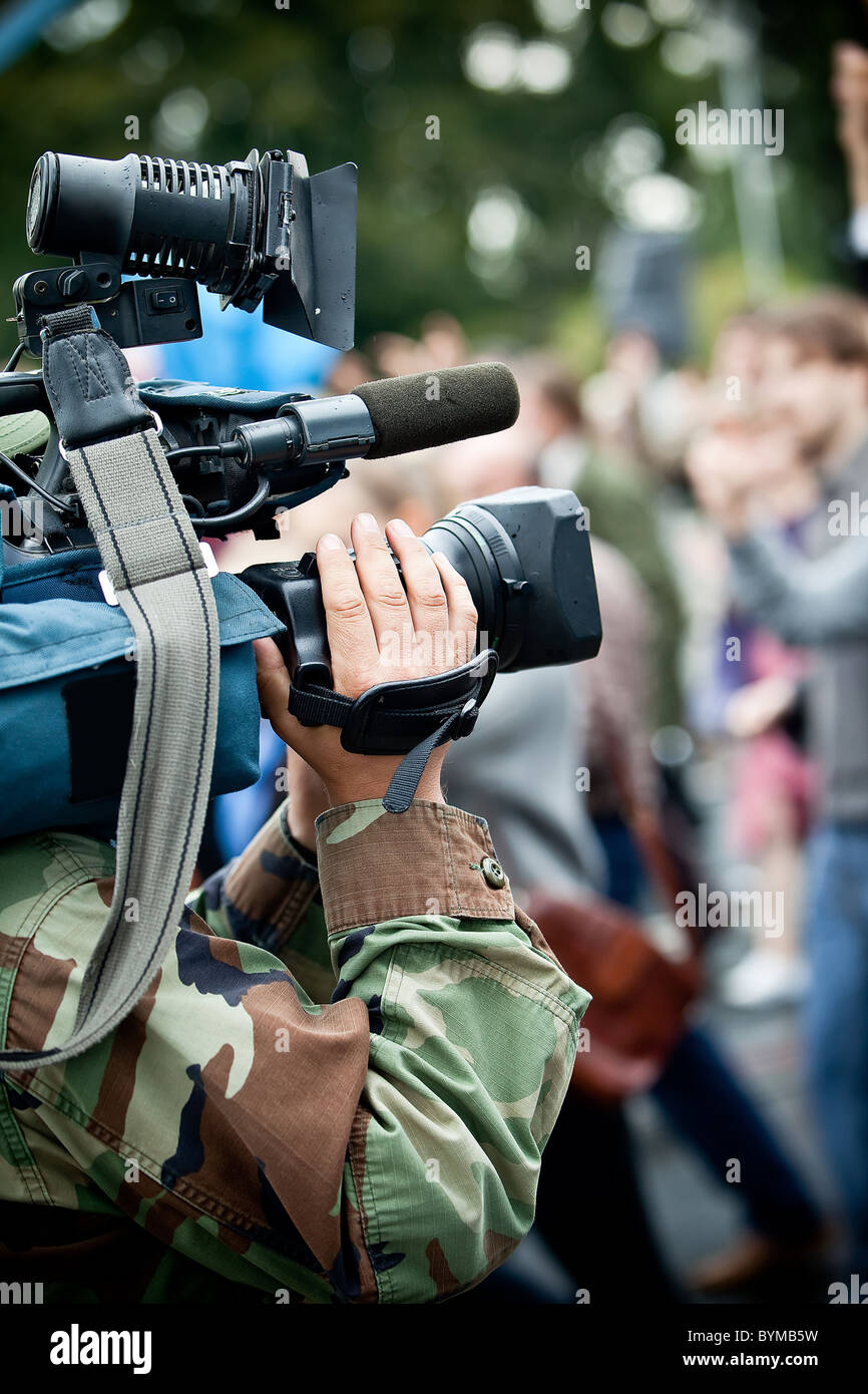 News maker on reportage recording with camcorder - Stock Image