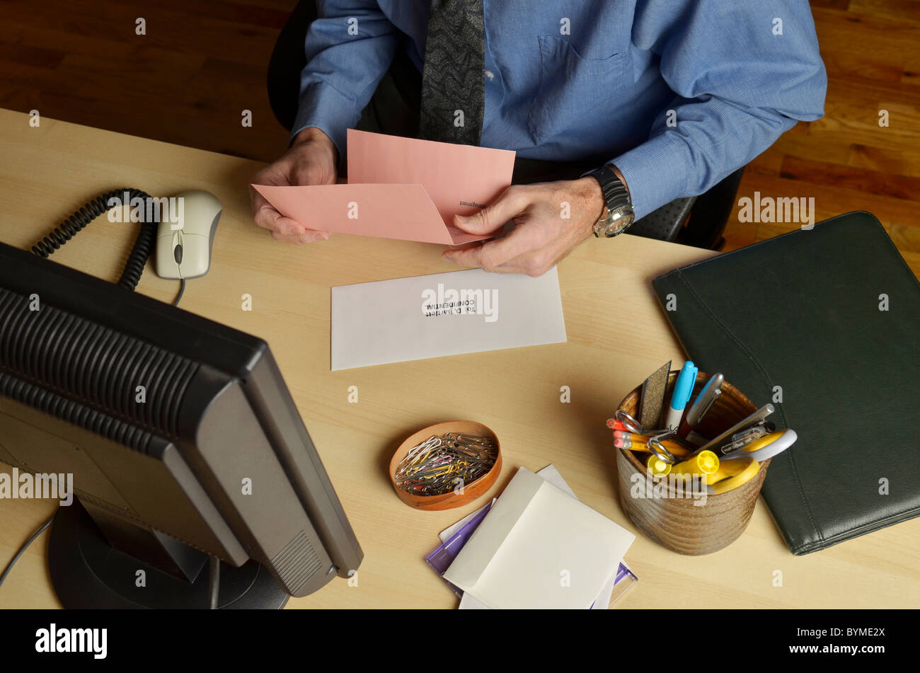 business man at desk holding pink slip - Stock Image