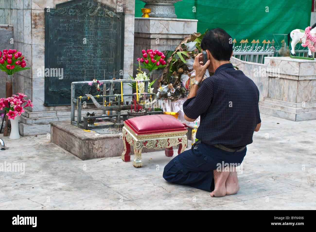 Worshiper at shrine talking on his mobile, Wat Mahannapharam Worawiharn, Bangkok, Thailand - Stock Image