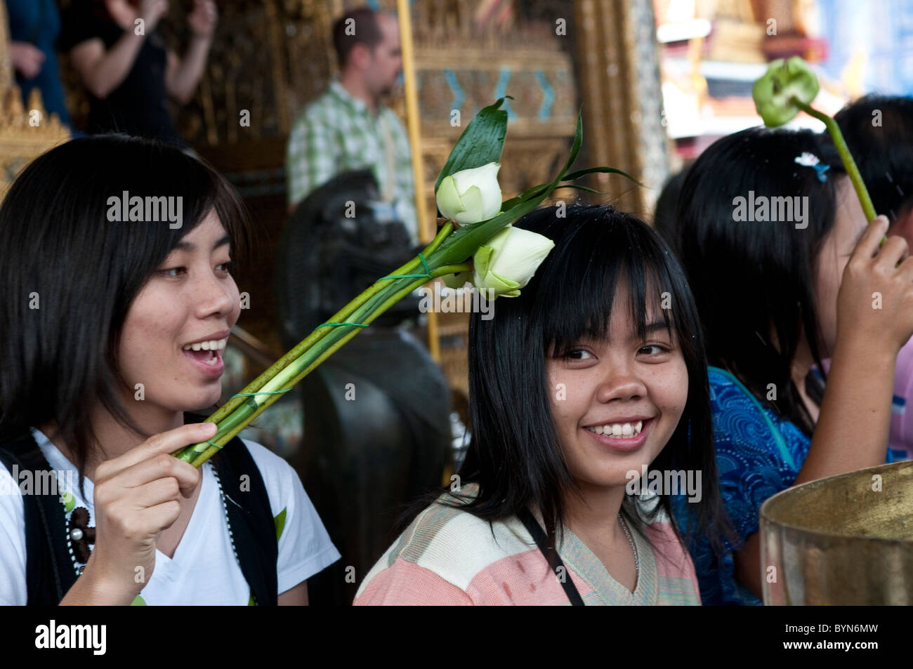 Worshipers with lotus flowers, Temple of Emerald Buddha, Wat Phra Kaeo, Grand Palace, Bangkok, Thailand - Stock Image