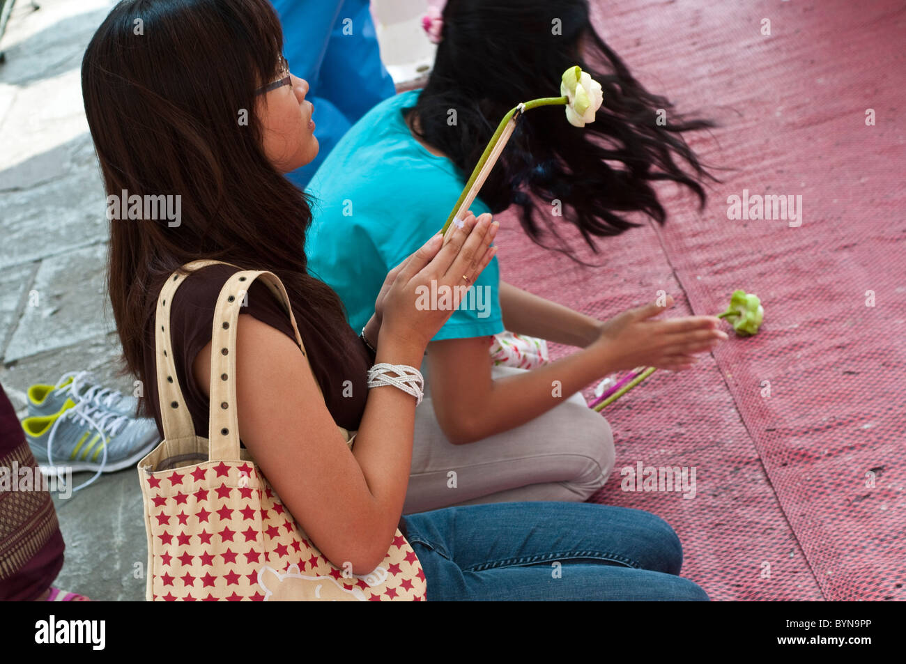 Worshipers praying at a shrine, Wat Phra Kaeo, Grand Palace, Bangkok, Thailand - Stock Image