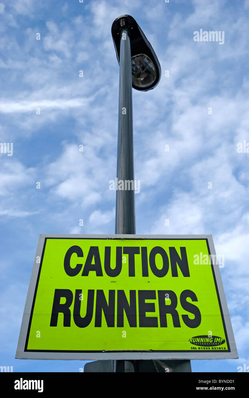 sign fixed to a lamppost warning caution runners, placed for an athletics event on the streets of teddington, middlesex, - Stock Image