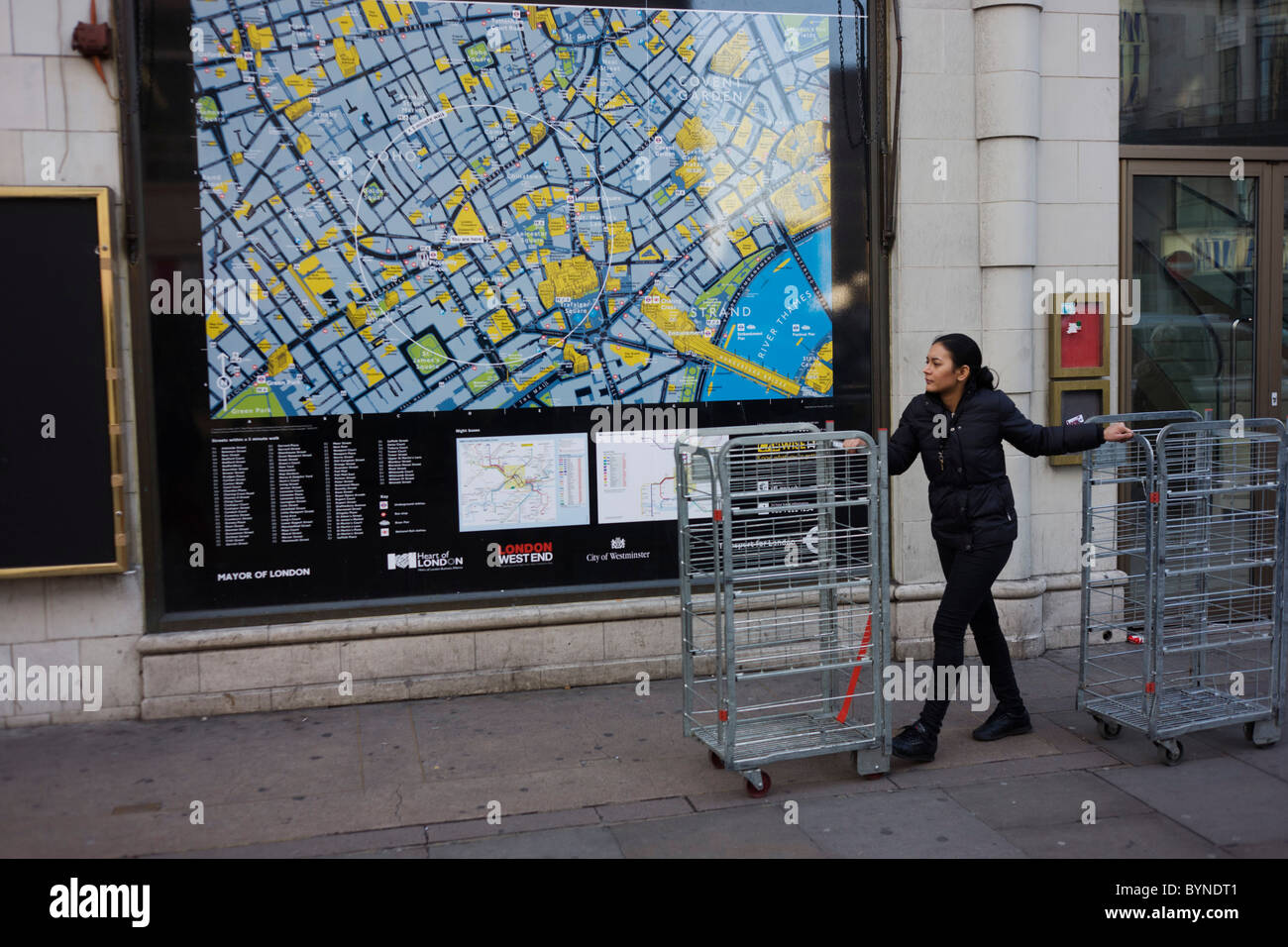 Woman walks two retail merchandise cages near a street map of London's West End. - Stock Image