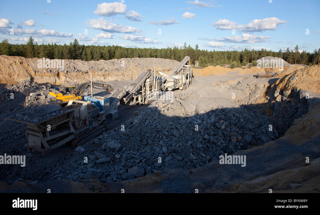 Rock crushing equipment and conveyor belt system at the bottom of a small rock quarry , Finland - Stock Image