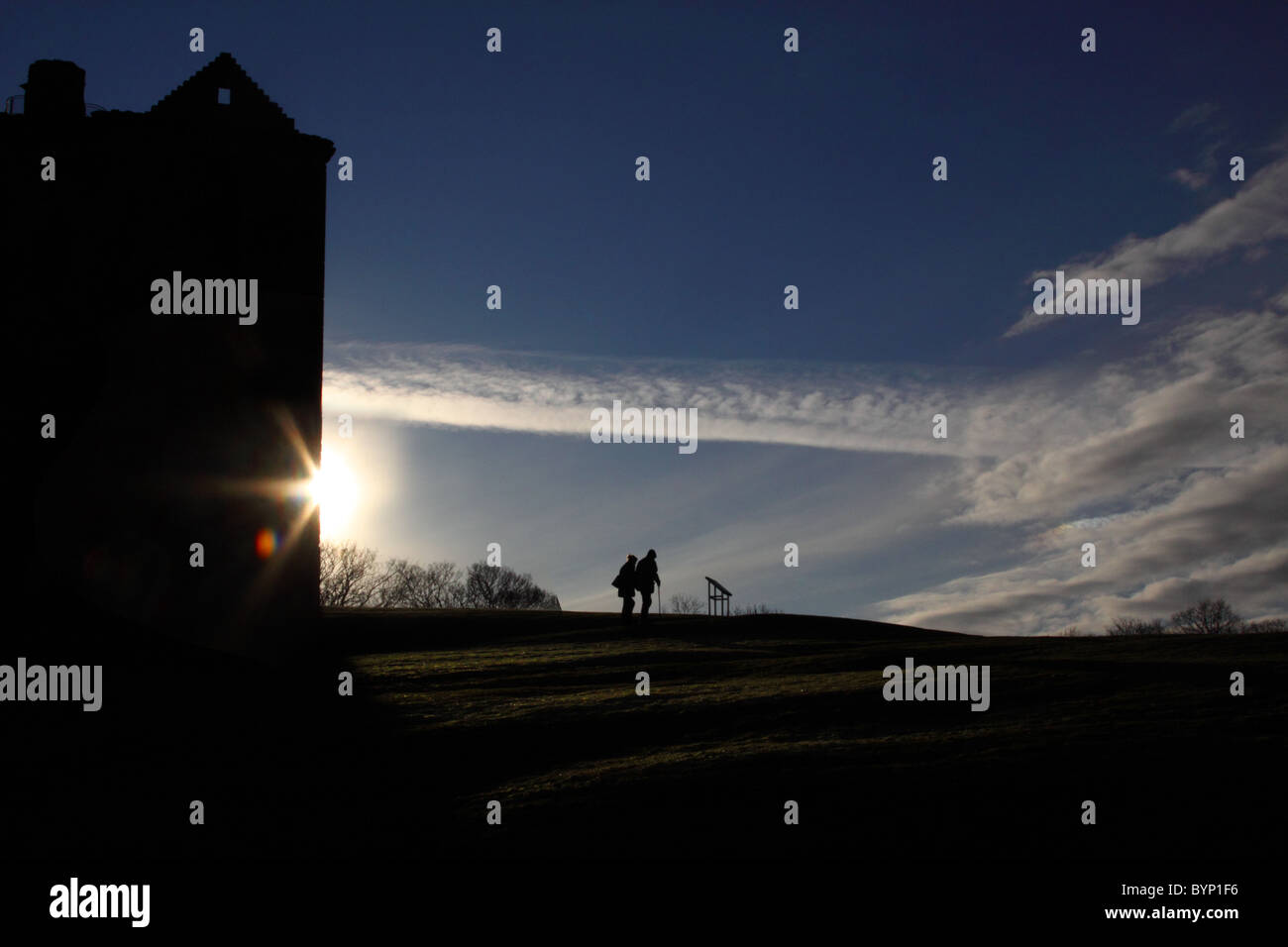 Silhouetted couple with the glare of the sun behind a building - Stock Image