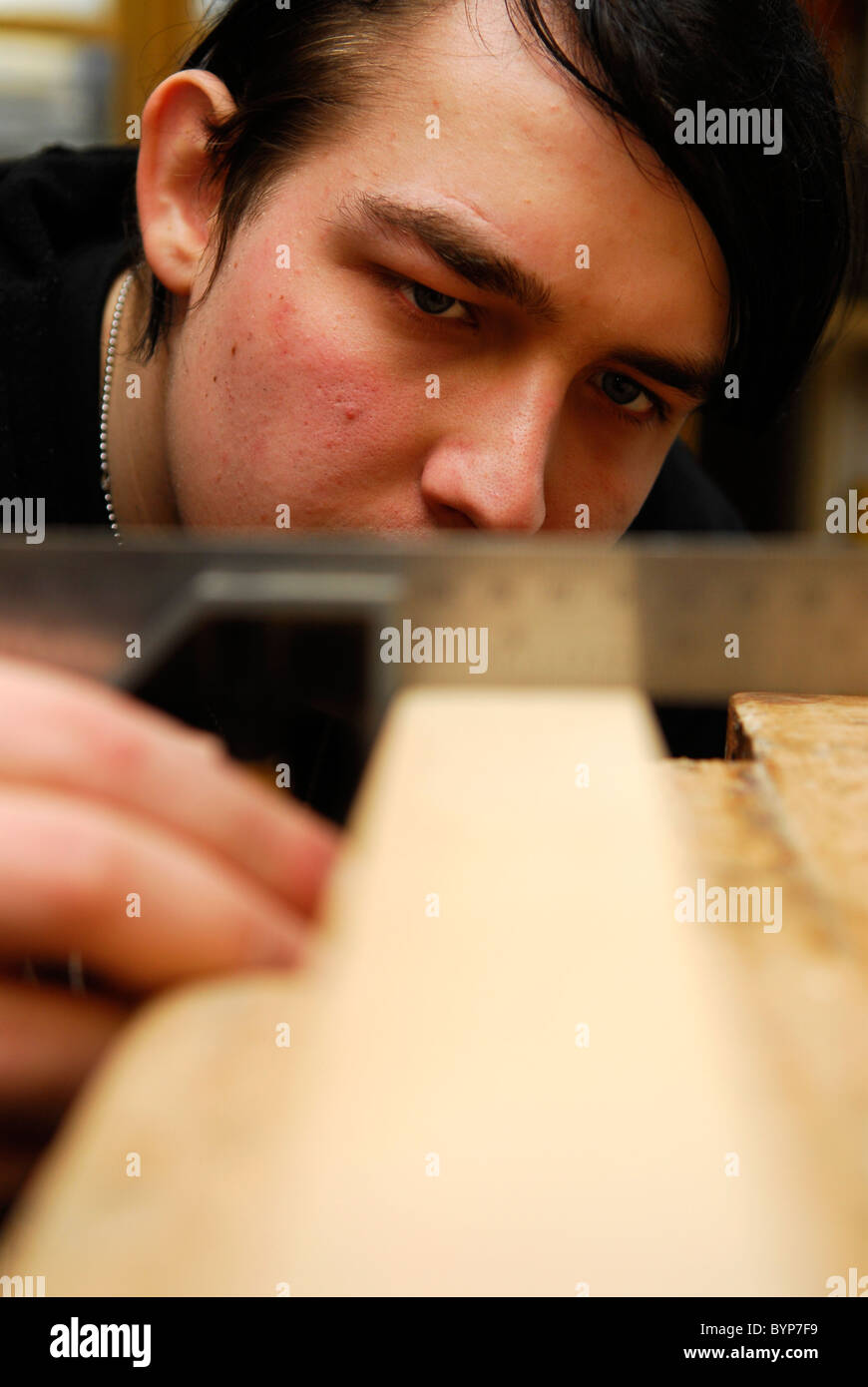 Young man gaining woodwork skills as part of an initiative to get young people into work, Bristol, UK. - Stock Image