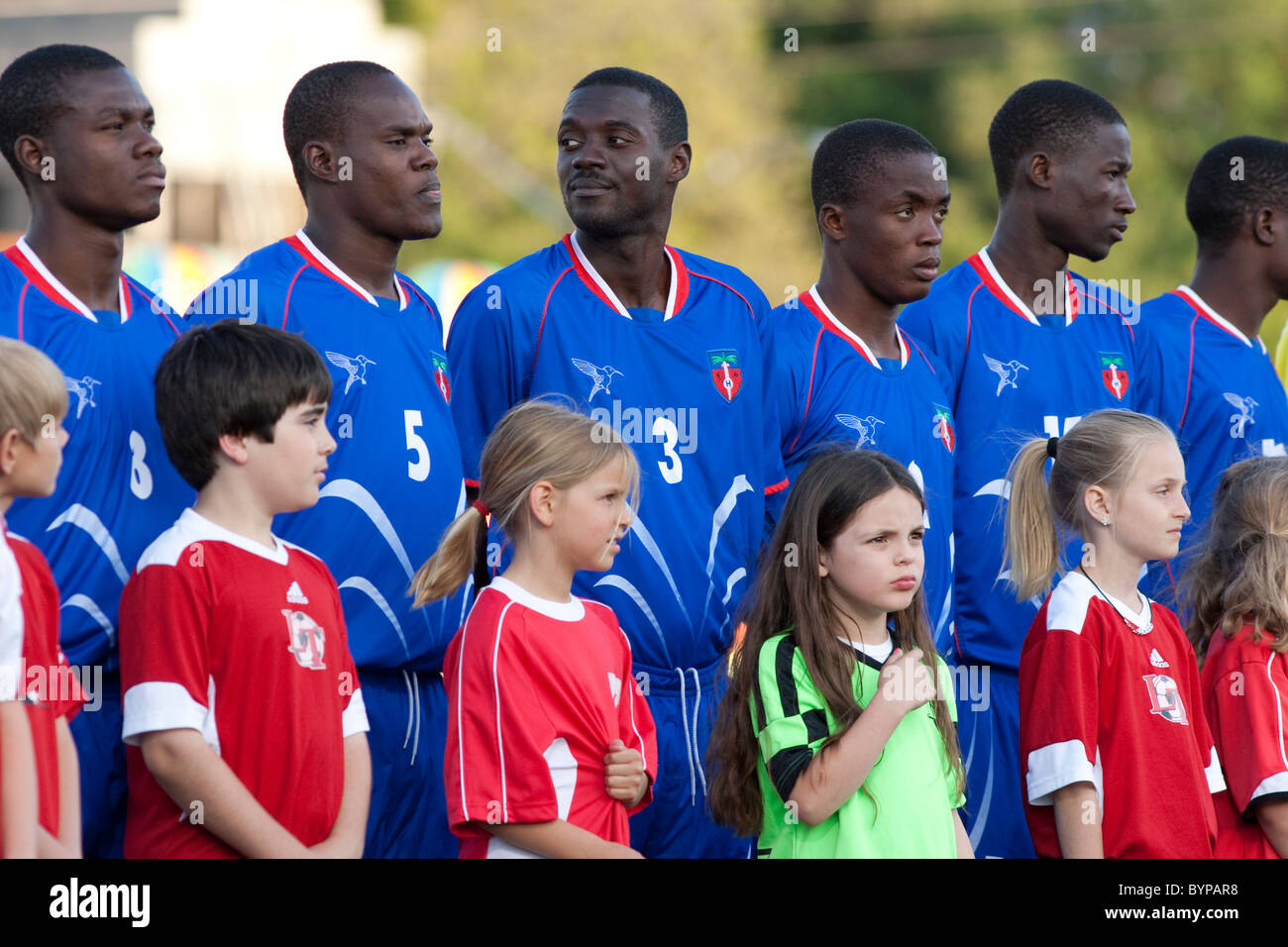 The Haitian National Soccer team and escorts stand at attention before an exhibition  with a professional team in - Stock Image